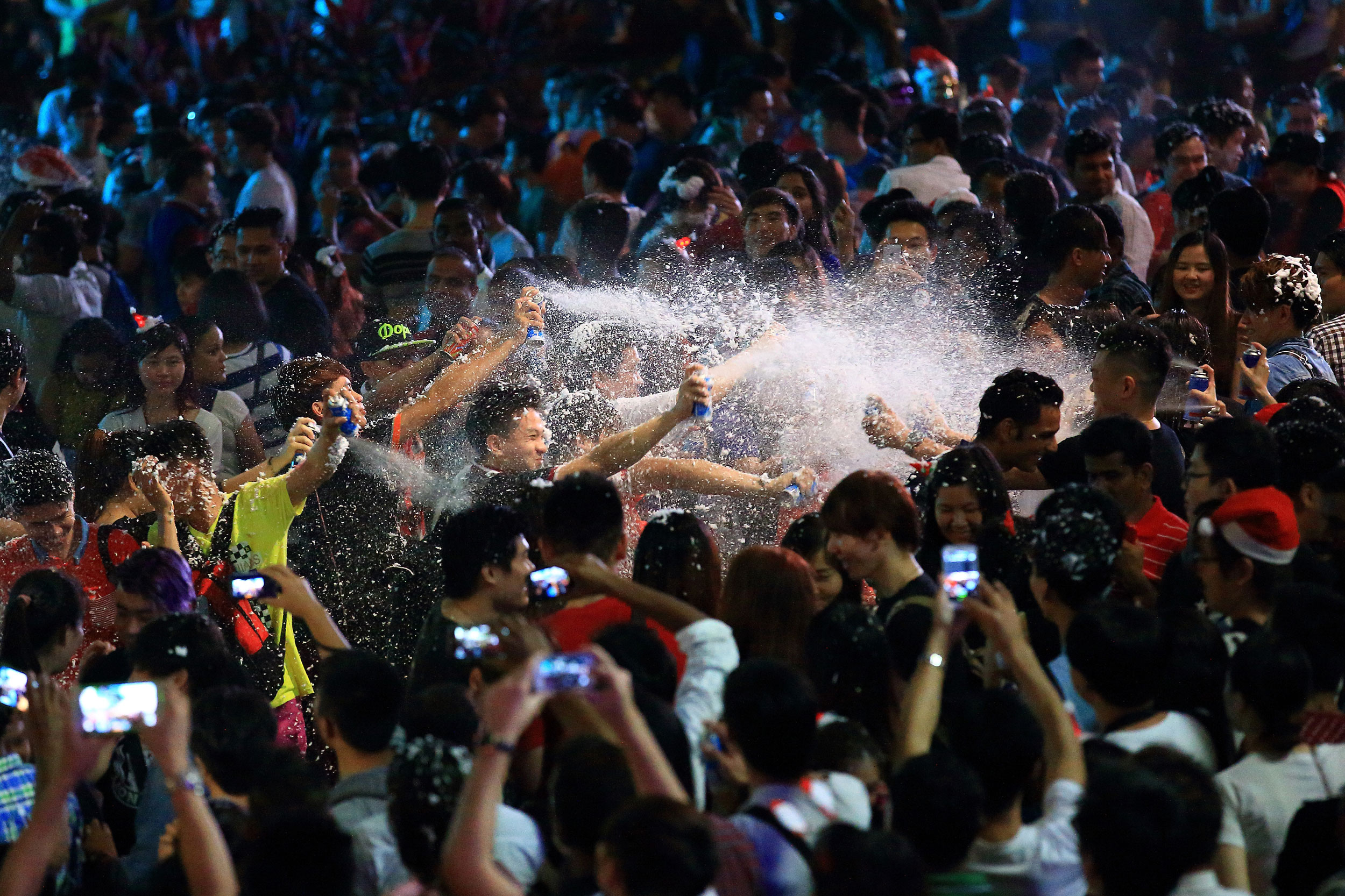 People spray synthetic snow at each other to usher in Christmas along Orchard Road on Dec. 25, 2014 in Singapore.