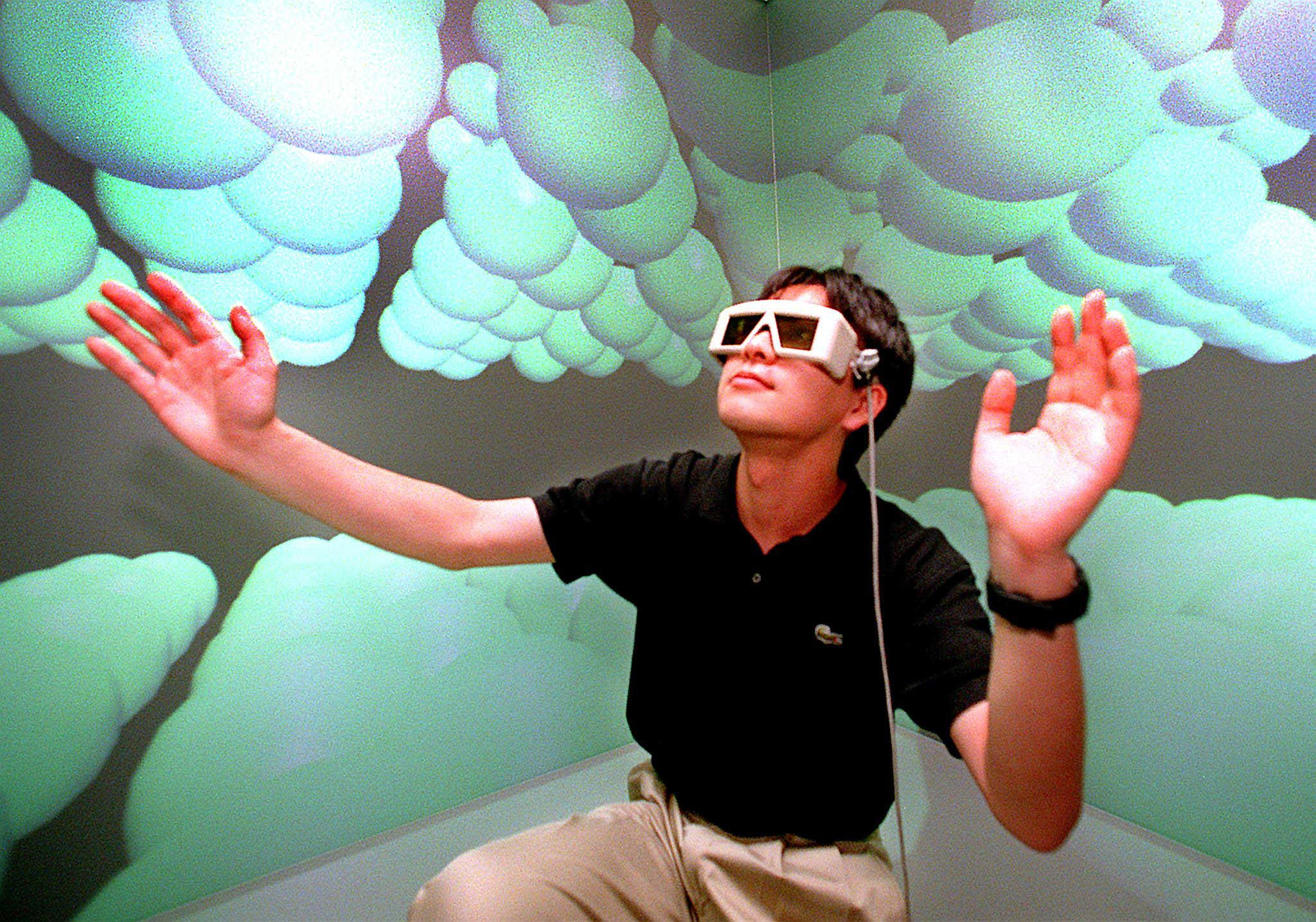 1998                                                              A researcher at Tokyo University's Intelligent Modeling Laboratory wearing 3-D glasses, extending his hands to touch carbon atoms in the microscopic world at the laboratory's virtual reality room.
