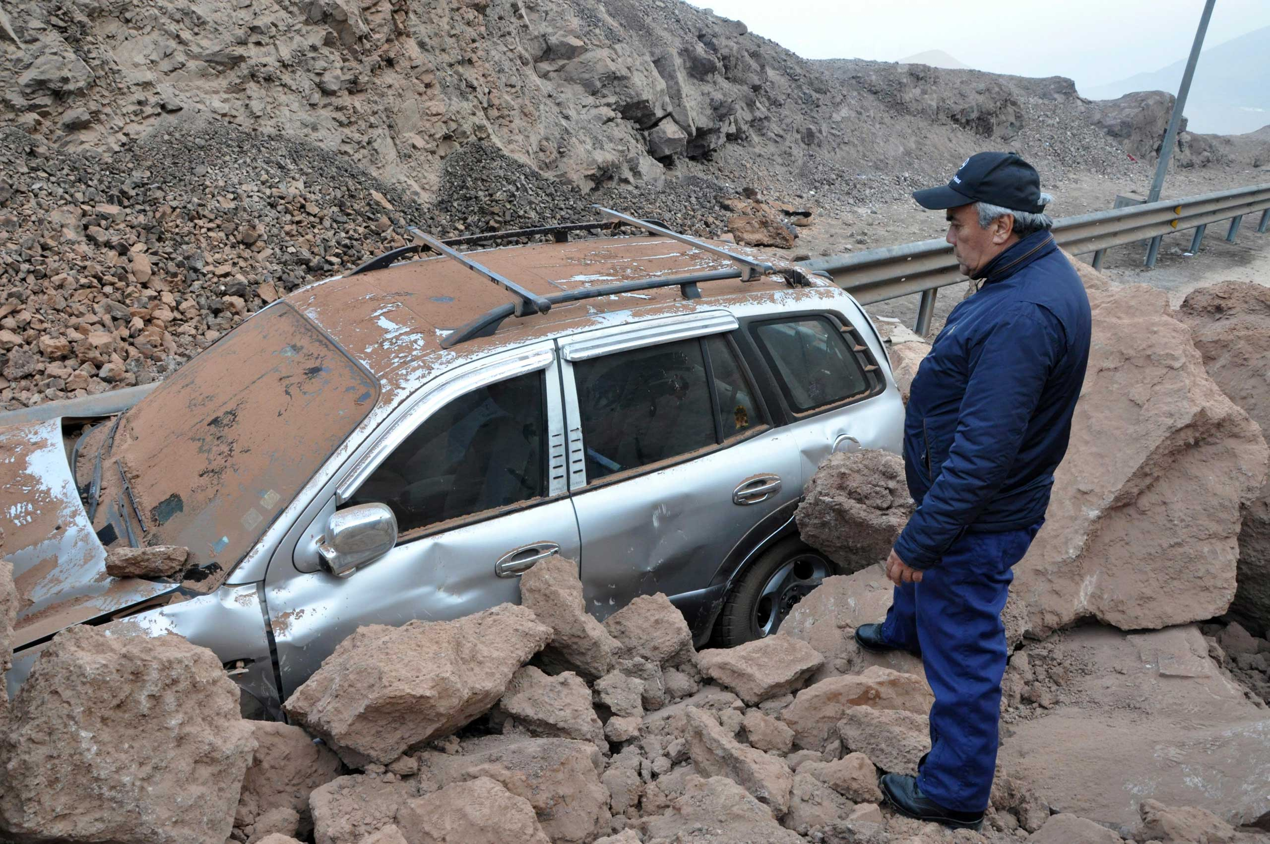 <b>Chile Earthquake</b> A rescue worker inspects a car caught under a landslide after an 8.2 magnitude earthquake and tsunami hit the northern port of Iquique, Chile on April 2, 2014.