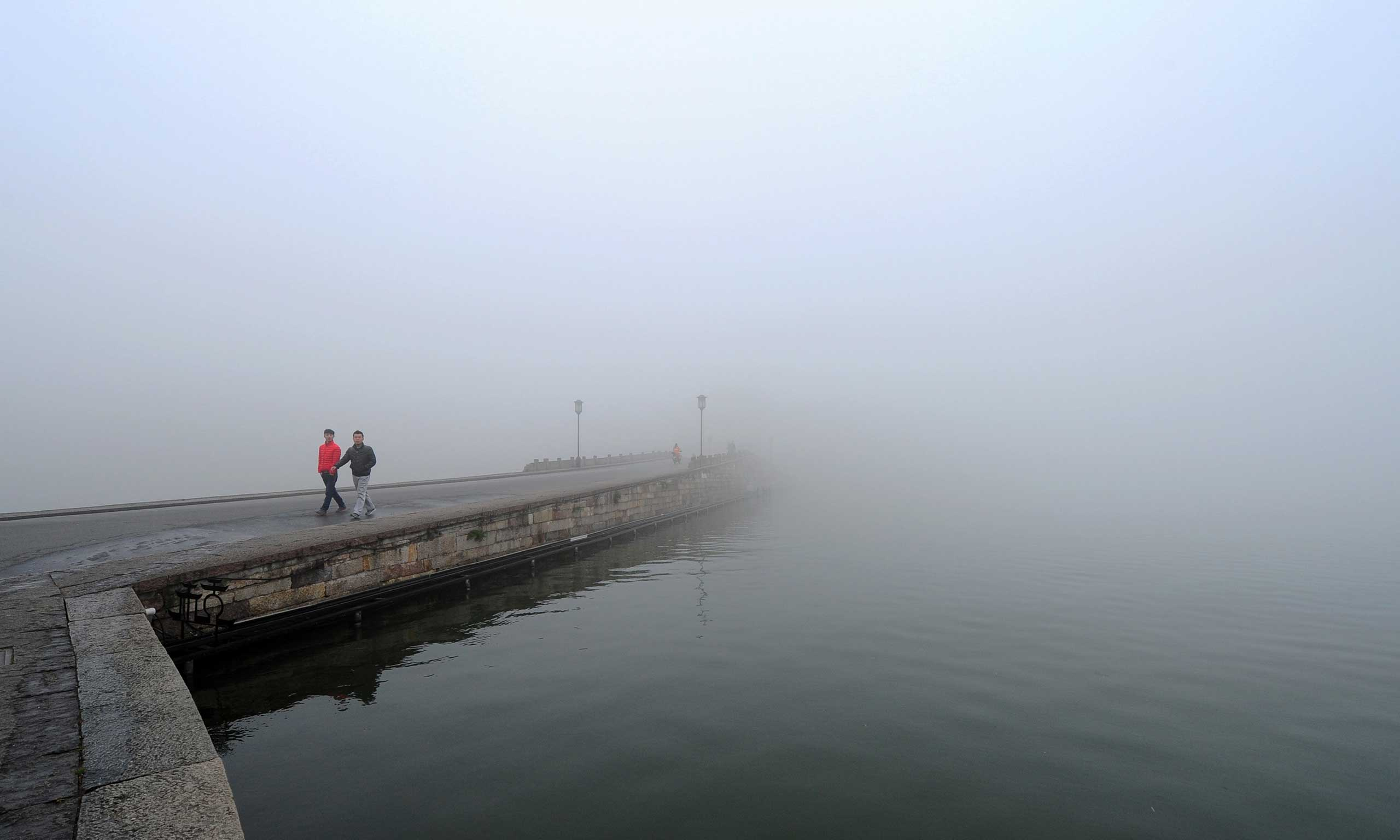 <b>China Smog</b> Tourists walk on the promenade along the bank of the West Lake in heavy smog in Hangzhou city, east China Zhejiang province on Jan. 31, 2014.