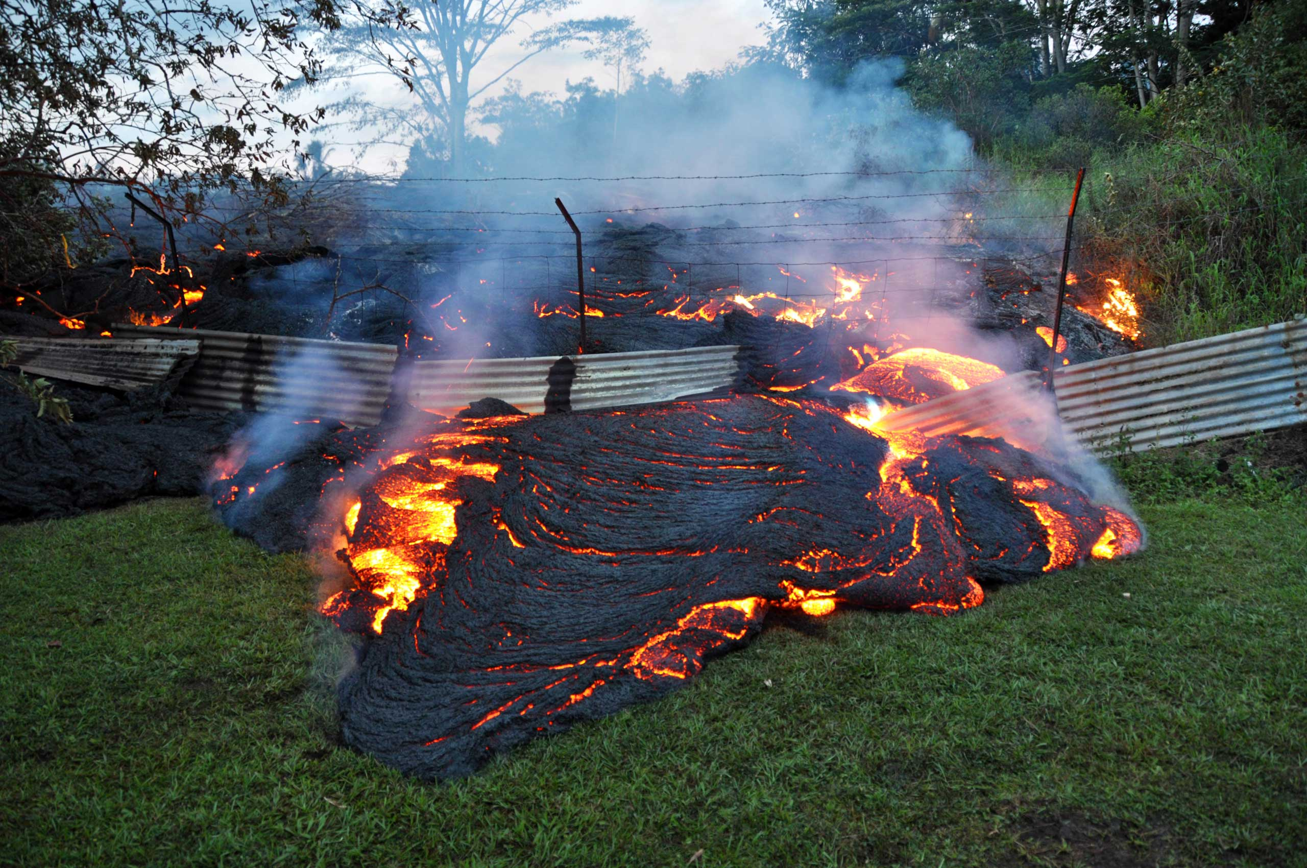 <b>Hawaii Lava</b> Lava pushes through a fence marking a property boundary above the town of Pahoa on the Big Island of Hawaii, Oct. 28, 2014.