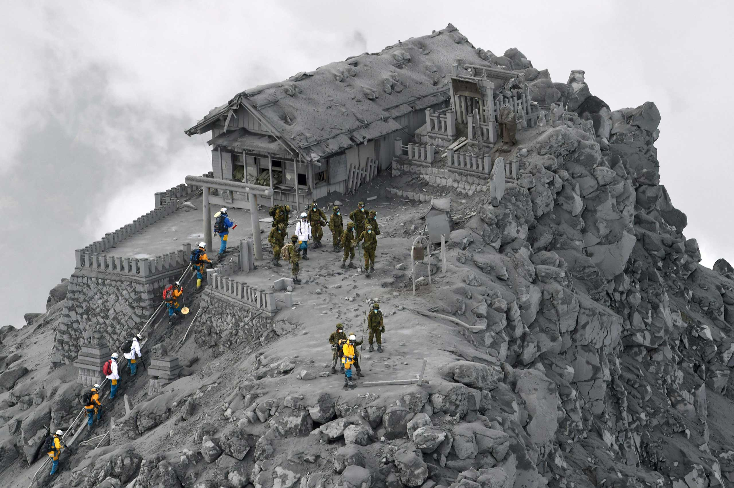 <b>Japan Volcano</b> Japan Ground Self-Defense Force personnel and other rescuers arrive to conduct search operations at the ash-covered Ontake Shrine near the summit of Mount Ontake in central Japan on Oct. 4, 2014.