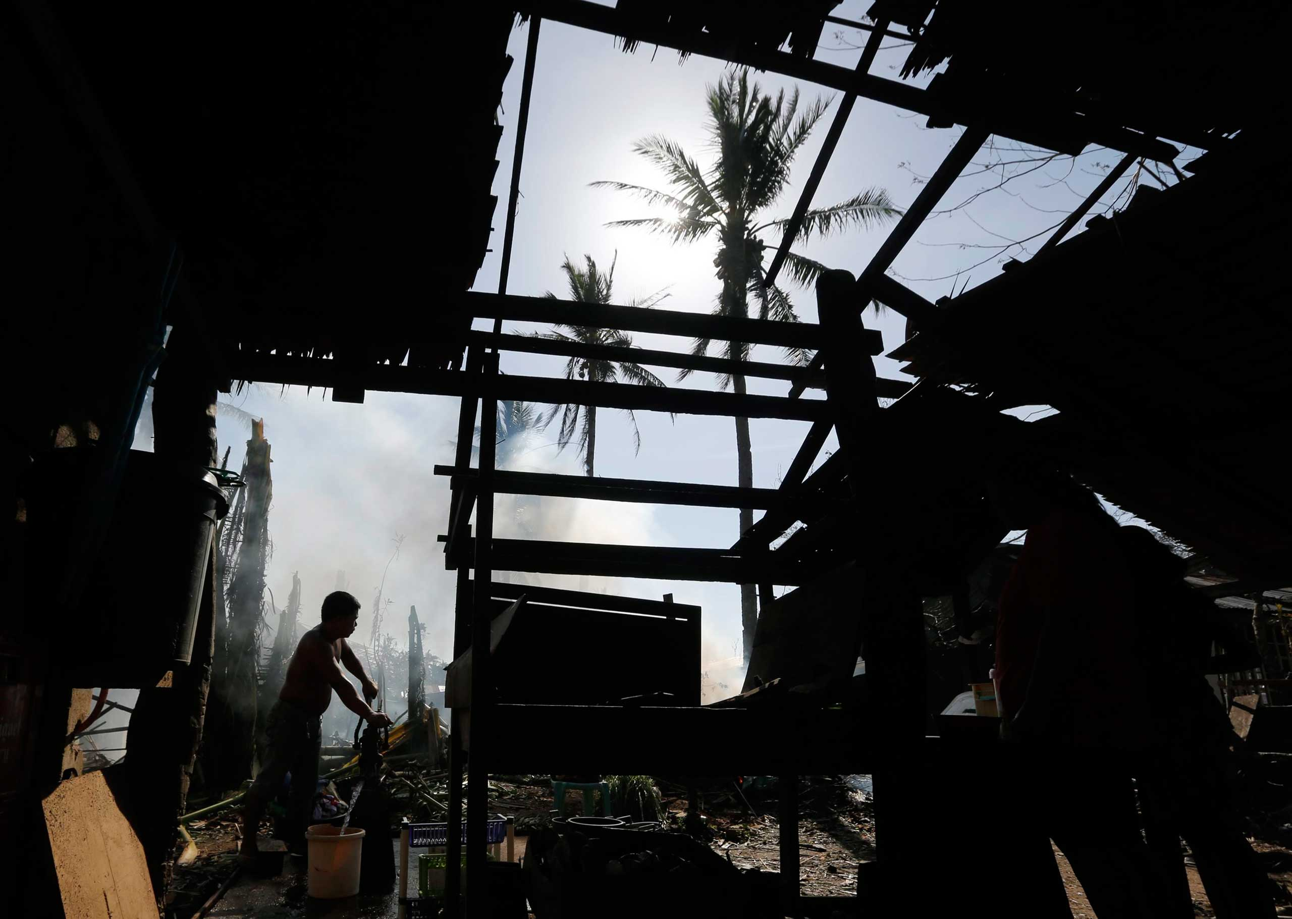 <b>Philippines Typhoon Hagupit</b> A Filipino typhoon victim collects water in front of a damaged home where Typhoon Hagupit hit, Samar Island, Philippines, on Dec. 8, 2014.