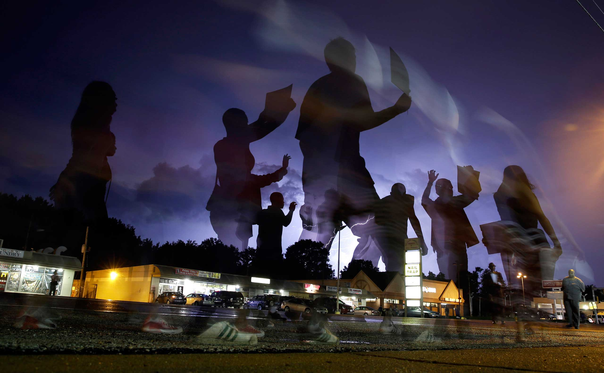 In this photo taken with a long exposure, protesters march in the street as lightning flashes in the distance in Ferguson, Mo., Aug. 20, 2014.