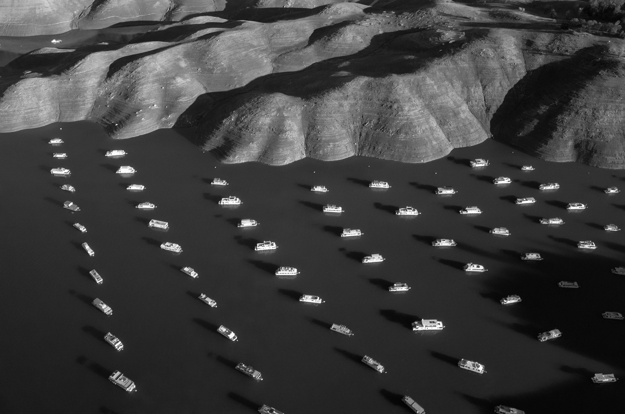 """Tomas van Houtryve. Lake Oroville, California. Nov. 25, 2014: """"I took this photo with my camera attached to an aerial drone as part of my 'Blue Sky Days' personal art project,"""" says VII photographer Tomas van Houtryve. """"During the past year I've traveled from coast to coast building a portrait of our country as seen from the sky. In addition to the unique point-of-view offered by this new technology, my project allows me to push back against what I consider to be a troubling trend: cameras are increasingly weaponized – used for surveillance, targeting and killing – rather than their traditional role as tools for portraiture, fine art and journalism. The rapid rise of drone technology means our sky will soon be buzzing with many more cameras.                                                              """"Do we want these robotic machines only to be scanning our faces and license plates for suspicious patterns, or we do want them documenting beauty, historic moments, and a hint of poetry as so many human photographers have since the invention of the camera?                                                              """"In this photograph, house boats are seen on Lake Oroville which is 70% empty due to California's severe drought. Much of the food eaten across the U.S. comes from California, and agriculture has been severely impacted by the scant snowpack and low rainfall of the past three years."""""""