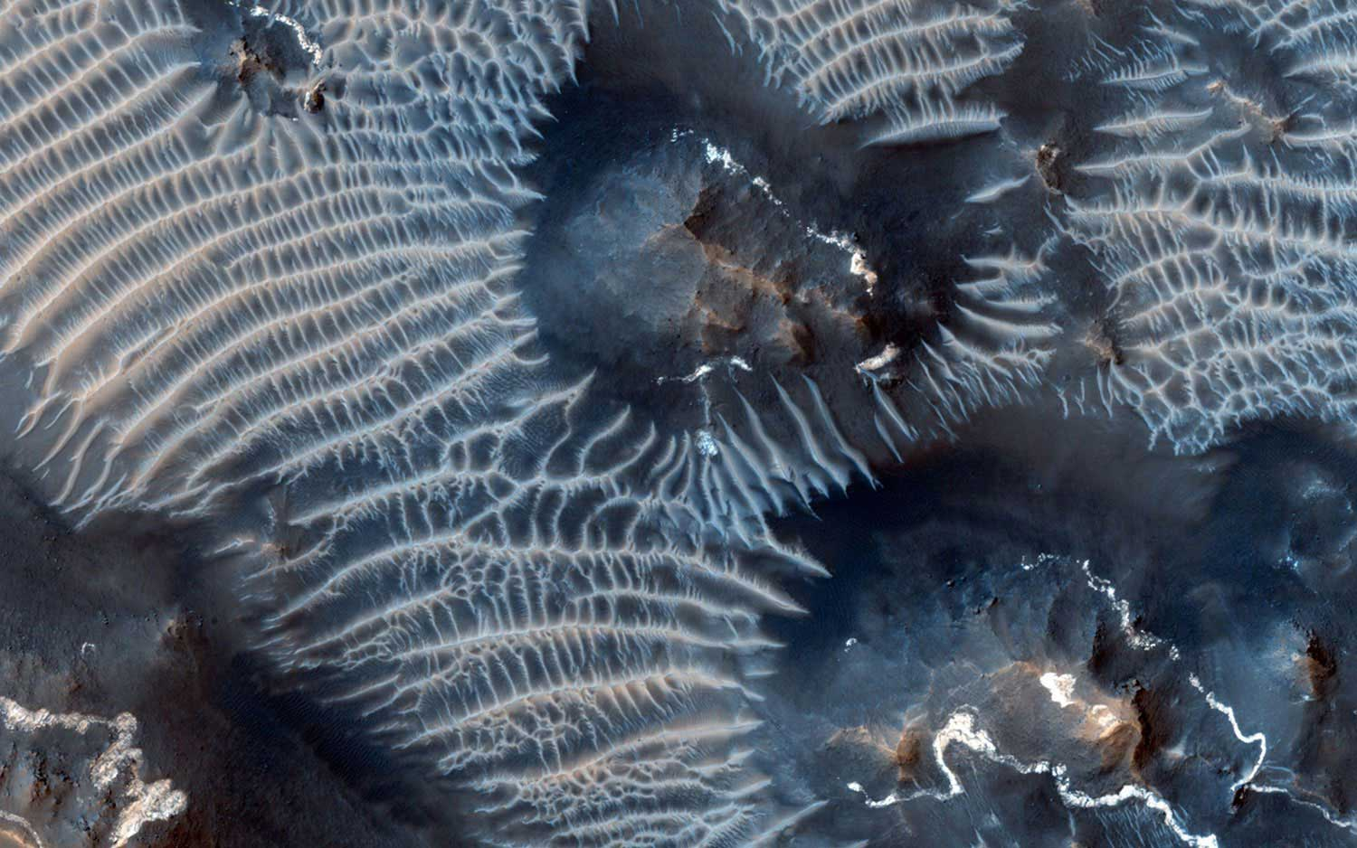 The Noctis Labyrinthus region of Mars, perched high in the Valles Marineris canyon system, as seen on Sept. 26, 2013. The image shows bright rimmed bedrock knobs, as well as two types of windblown sediments.