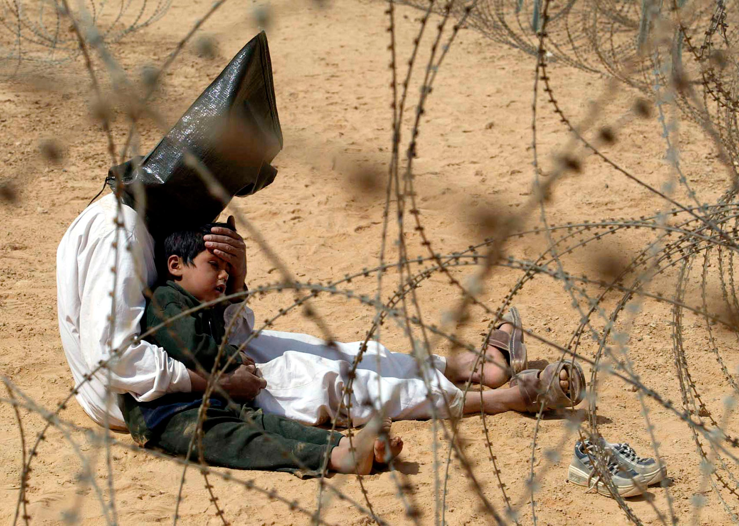 An Iraqi prisoner of war comforts his 4-year-old son at a regroupment center for POWs of the 101st Airborne Division near An Najaf on March 31, 2003. The man was seized in An Najaf with his son, and the U.S. military did not want to separate them.