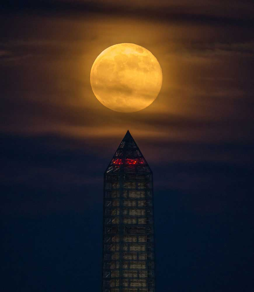 A supermoon rises behind the Washington Monument, on June 23, 2013, in Washington, D.C. This year the Supermoon was up to 13.5% larger and 30% brighter than a typical Full Moon is. This is a result of the Moon reaching its perigee—the closest that it gets to the Earth during the course of its orbit.