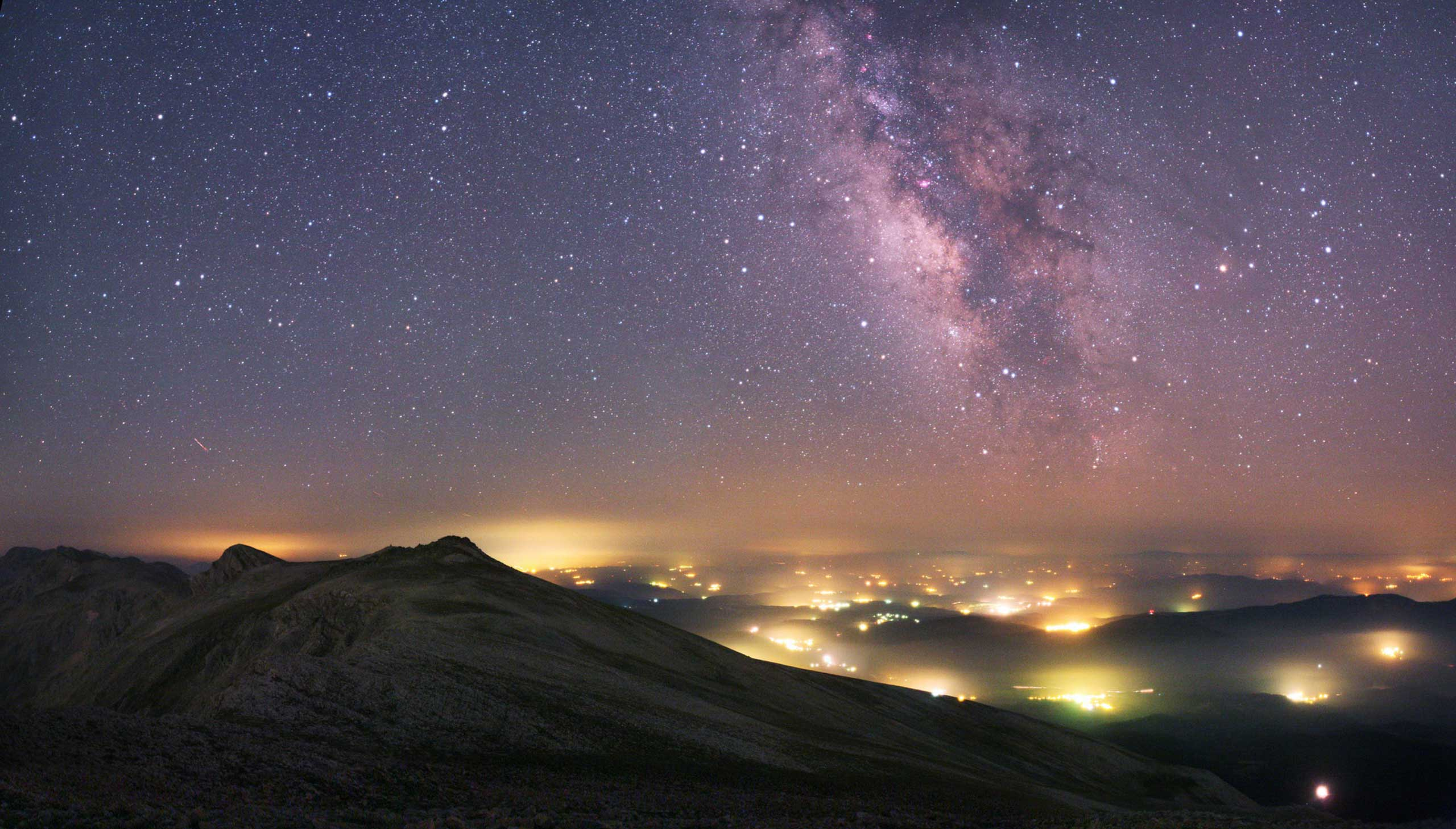 Dark mountain peaks frame two distinct lightscapes - the distant glow of towns and villages, and the majestic star fields of The Milky Way. Making the most of an August night, the photographer got this shot after trekking out to the Uludag National Park near his hometown of Bursa, Turkey.