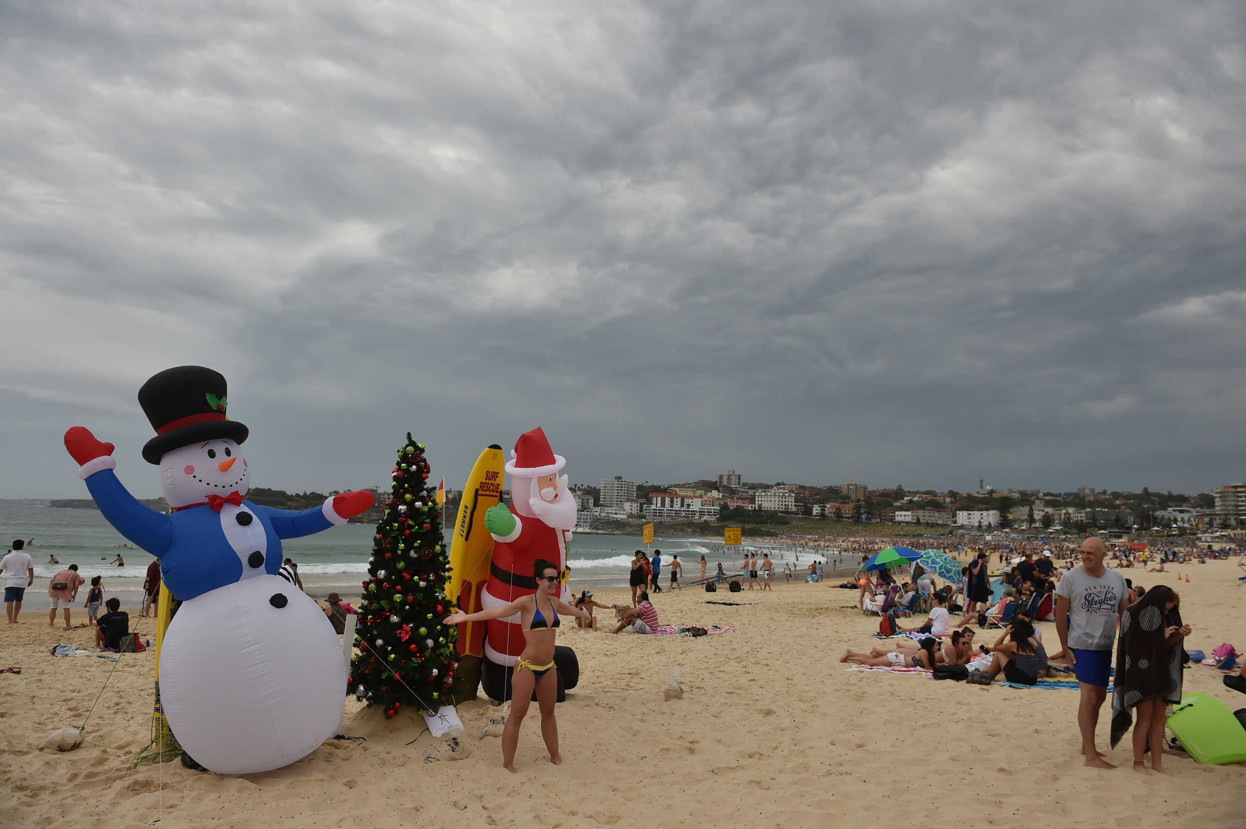 Visitors take photos in front of an inflatable snow man and Santa Claus on Bondi Beach on Christmas Day on Dec. 25, 2014.