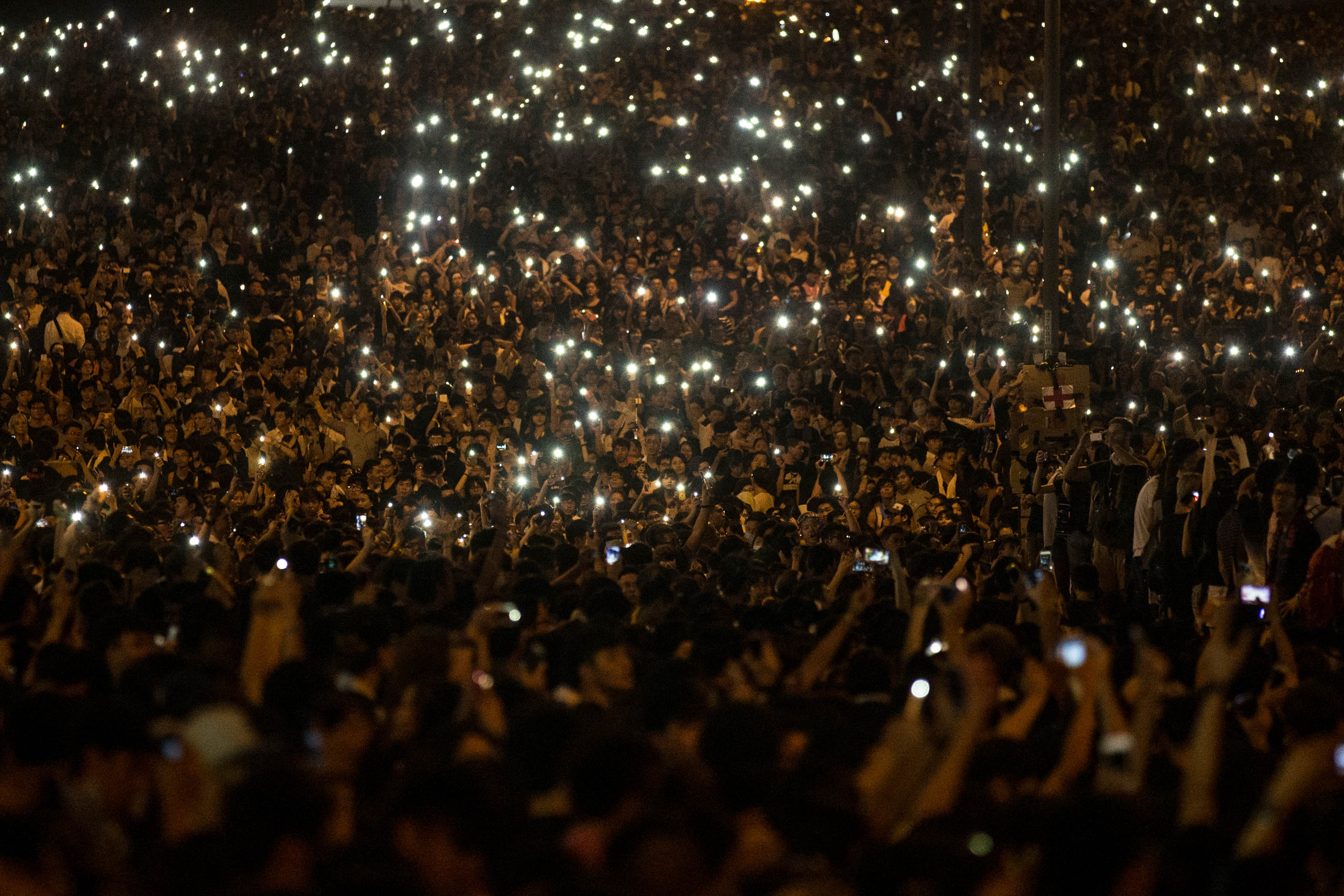 HONG KONG - SEPTEMBER 29:  Protesters wave their cell phones in the air in the streets outside the Hong Kong Government Complex on September 29, 2014 in Hong Kong, Hong Kong. Thousands of pro democracy supporters have remained in the streets of Hong Kong for another day of protests. Protestors are unhappy with Chinese government's plans to vet candidates in Hong Kong's 2017 elections.  (Photo by Chris McGrath/Getty Images)