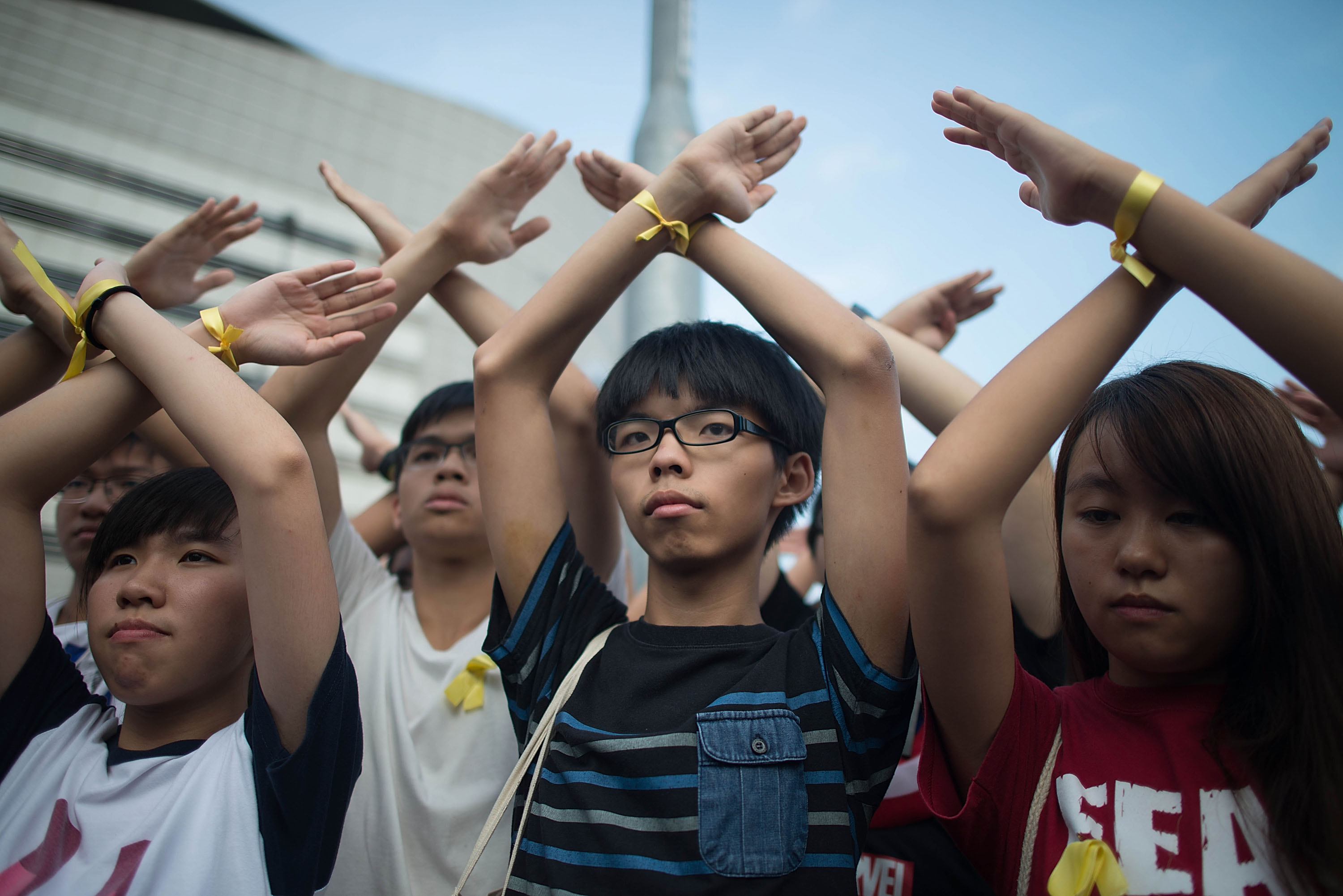 Student pro-democracy group Scholarism convenor Joshua Wong (C) makes a gesture at the Flag Raising Ceremony at Golden Bauhinia Square on October 1, 2014 in Hong Kong.