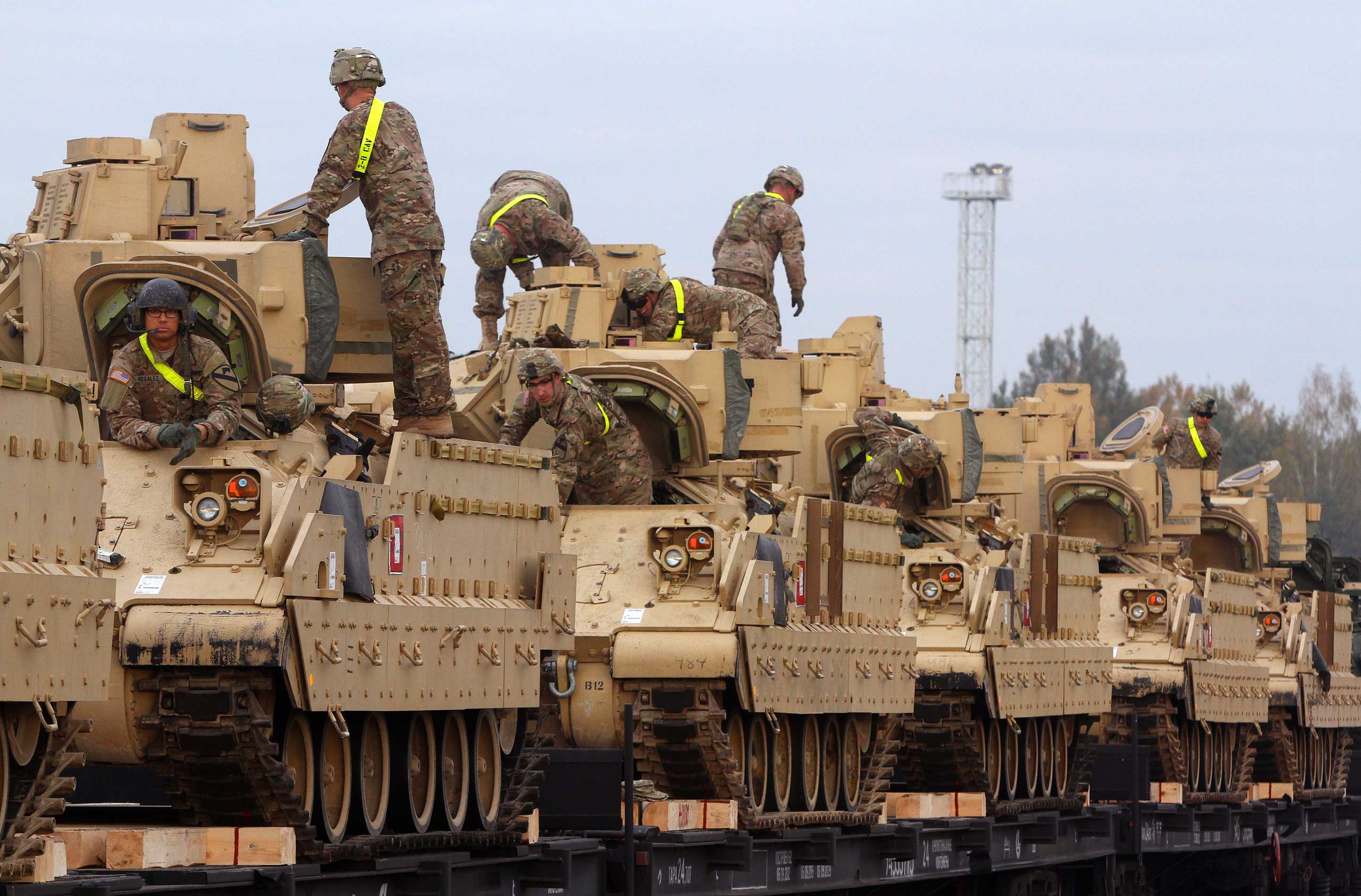 Members of the US Army 1st Brigade, 1st Cavalry Division, transport heavy combat equipment including Bradley Fighting Vehicles at the railway station near the Rukla military base in Lithuania, Oct. 4, 2014.