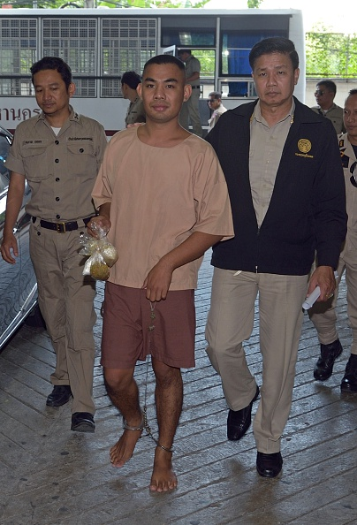 Thai university student Patiwat Saraiyaem, center, is escorted by prison officials as he arrives at the criminal court in Bangkok on Oct. 27, 2014