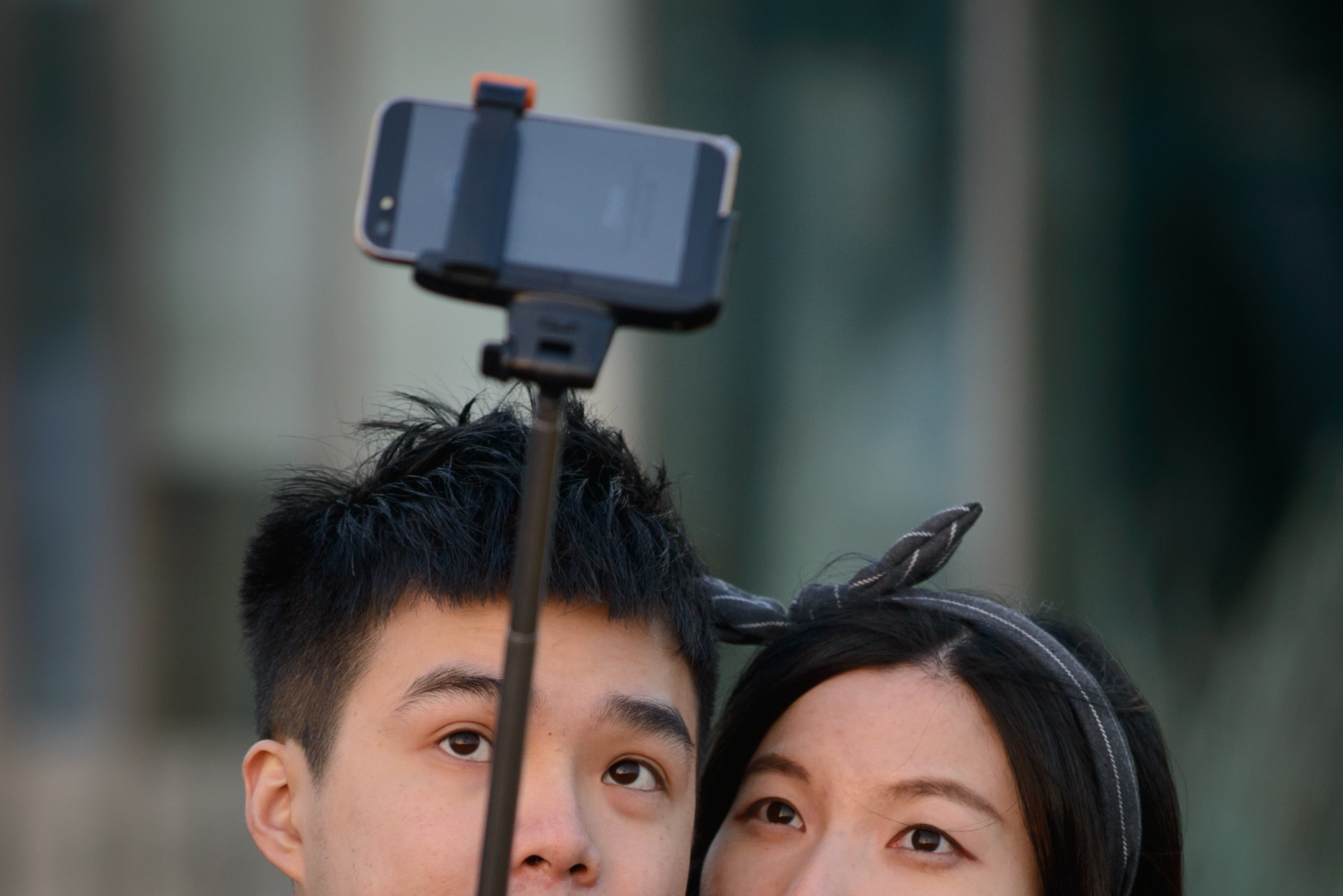In a photo taken on November 26, 2014 a couple use a 'selfie stick' to take a photo at a popular tourist spot in Seoul.