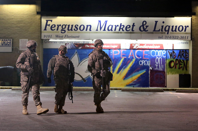 Missouri National Guard soldiers patrol the parking lot of the Ferguson Market & Liquor store on West Florissant Avenue in Ferguson a little after 10 p.m. on Dec. 1, 2014.