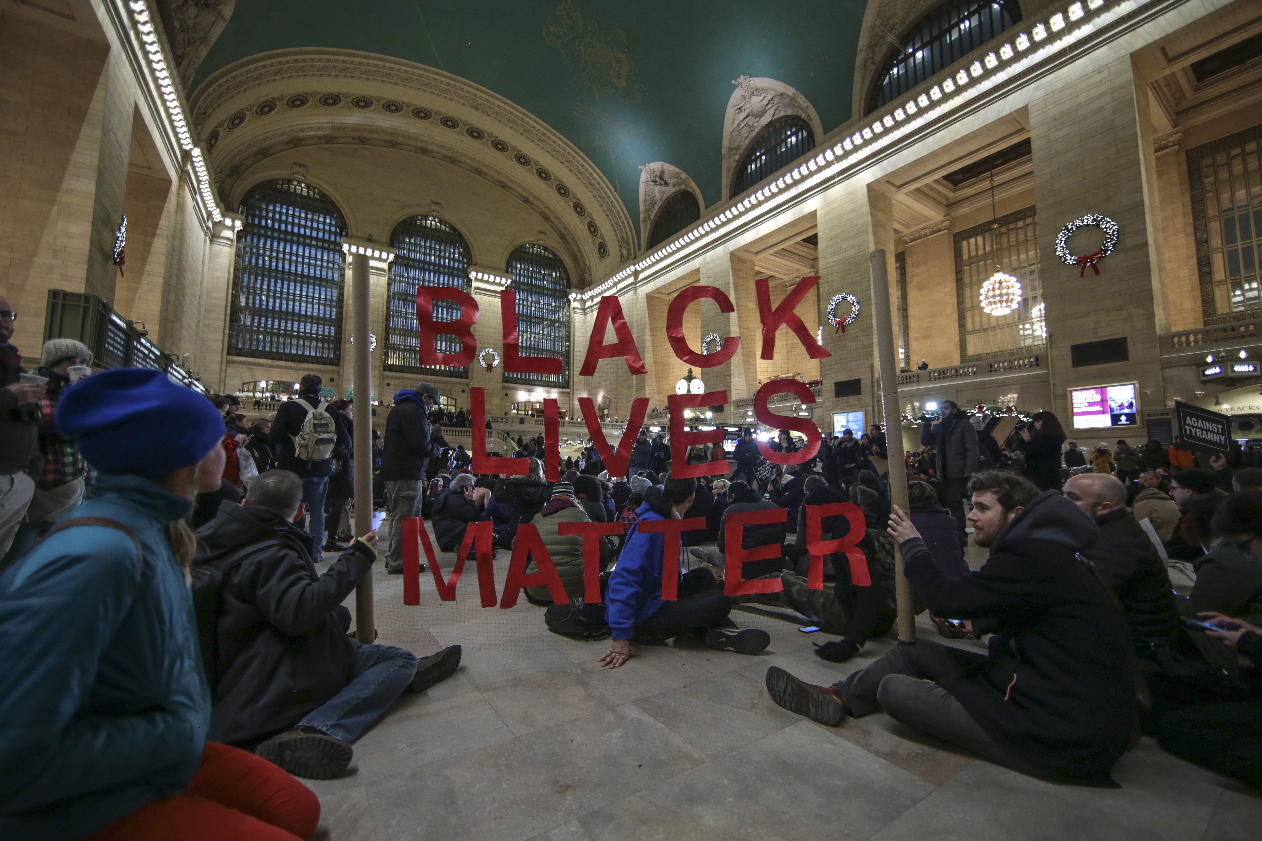 Protesters hold a banner during a protest at Grand Central Terminal after a grand jury decided not to indict a police officer involved in the death of  Eric Garner in July on December 7, 2014 in New York, N.Y. Protests are being staged nationwide after grand juries investigating the deaths of Michael Brown in Ferguson, Missouri and Eric Garner in New York failed to indict the police officers involved in both incidents.