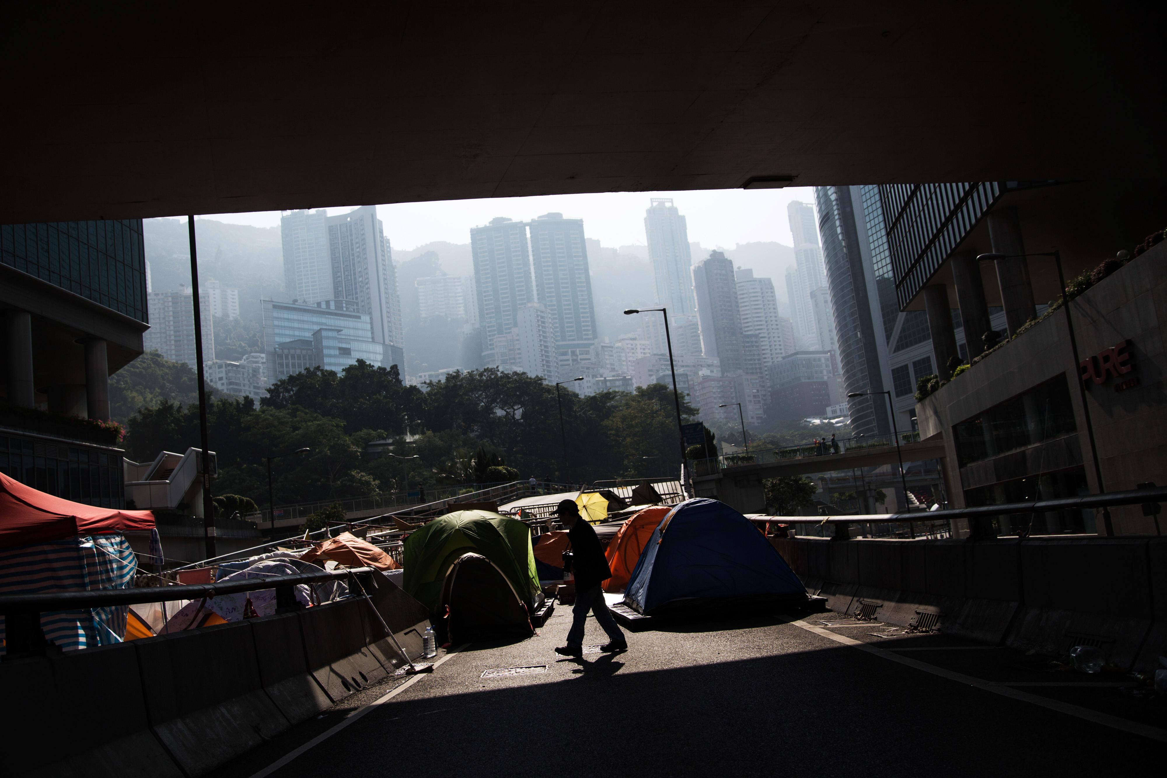 A man is silhouetted walking past tents on a flyover in the Admiralty district of Hong Kong on Dec. 9, 2014. Pro-democracy demonstrators in Hong Kong are bracing for police to clear part of their main protest site in two days following a court order to reopen roads that have been occupied for more than two months