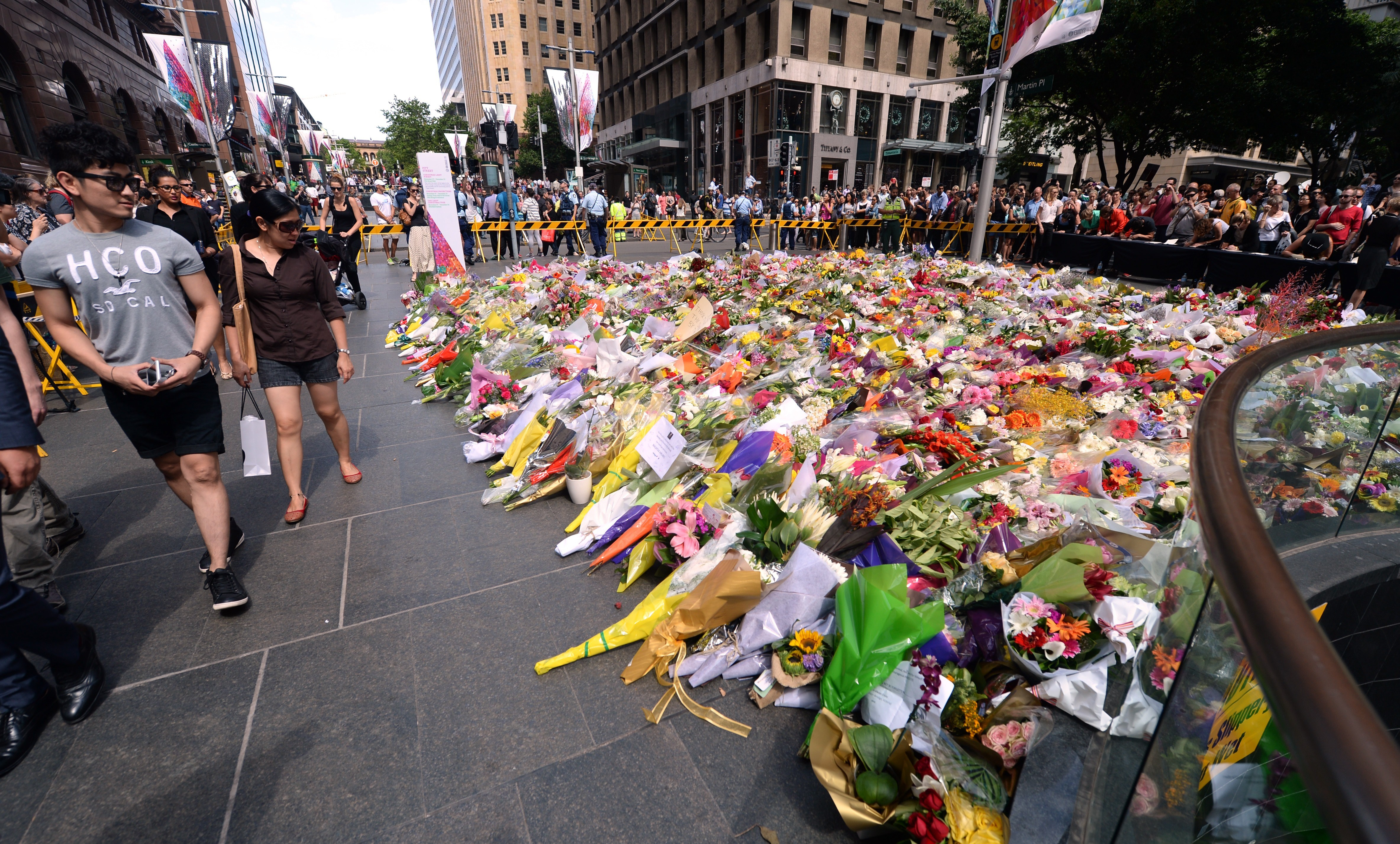 Visitors look at a makeshift memorial near the scene of the fatal siege in the heart of Sydney's financial district on Dec. 16, 2014. Sydneysiders including tearful office workers and Muslim women in hijabs laid flowers at the scene in an outpouring of grief and shock