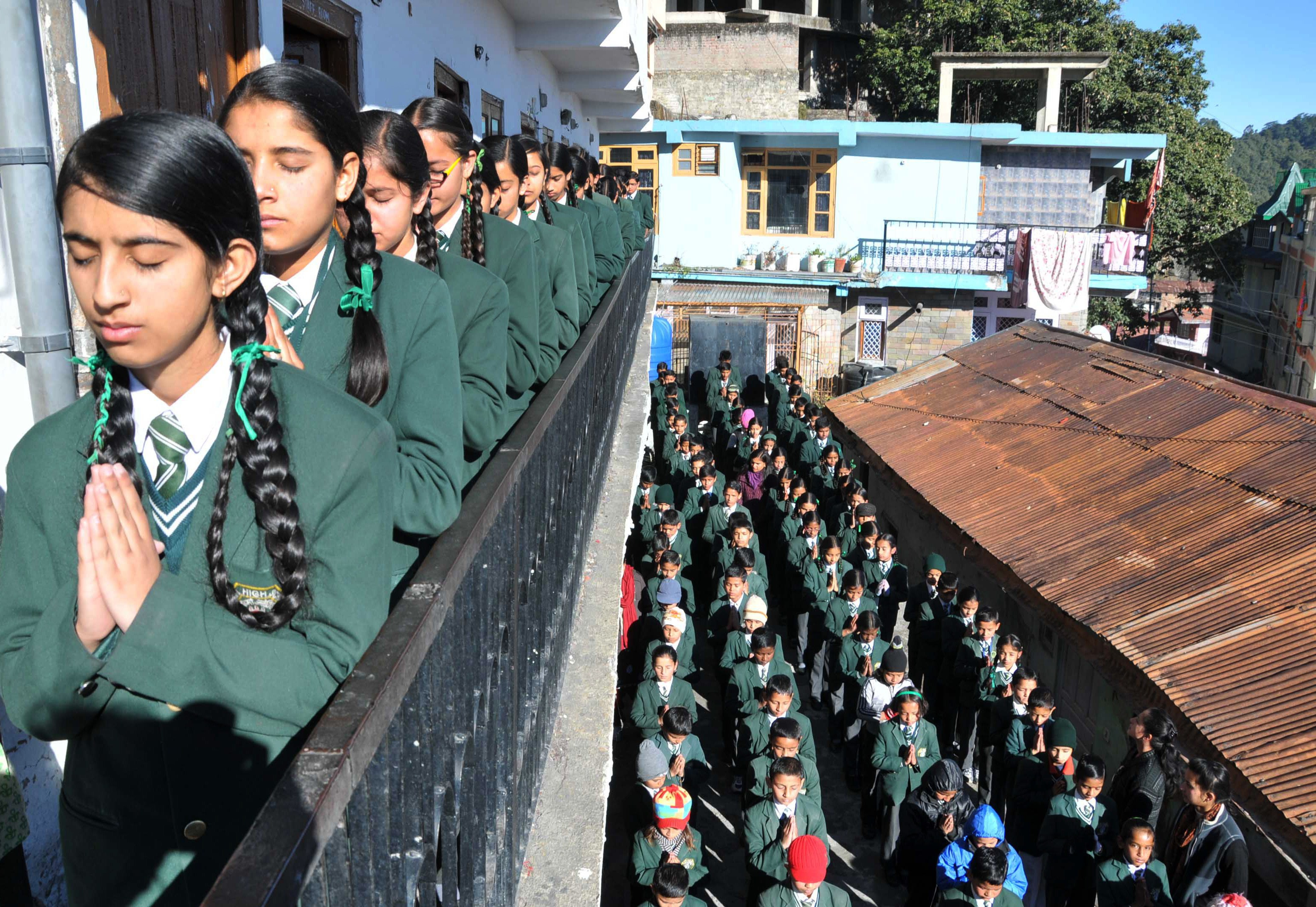 Schoolchildren pray during morning assembly at their school in Shimla, India, on Dec. 17, 2014, as they pay tribute to slain students and staff after an attack on an army school in Peshawar, Pakistan
