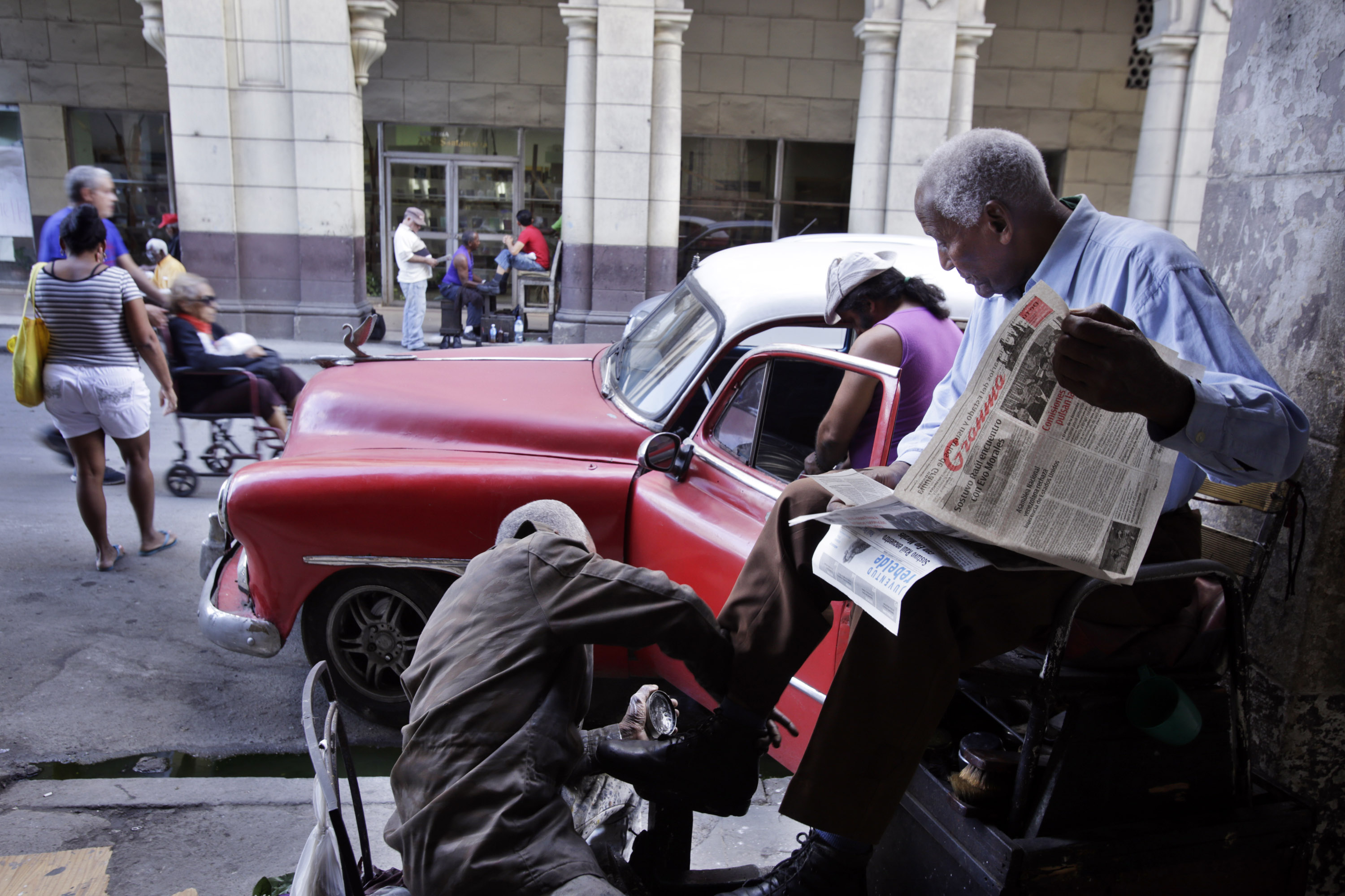 A Cuban man reads the Granma, a Cuban communist party paper, as he has his shoes shined, shortly after a live broadcast a speech by Cuban President Raul Castro about the re-establishment of  official diplomatic relations with the U.S., on December 17, 2014, in Havana, Cuba.