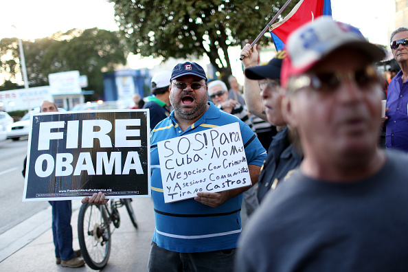 People stand outside the Little Havana restaurant Versailles, as they absorb the news that Alan Gross was released from a Cuban prison and that U.S. President Barack Obama wants to change the United States Cuba policy on Dec. 17, 2014 in Miami, United States