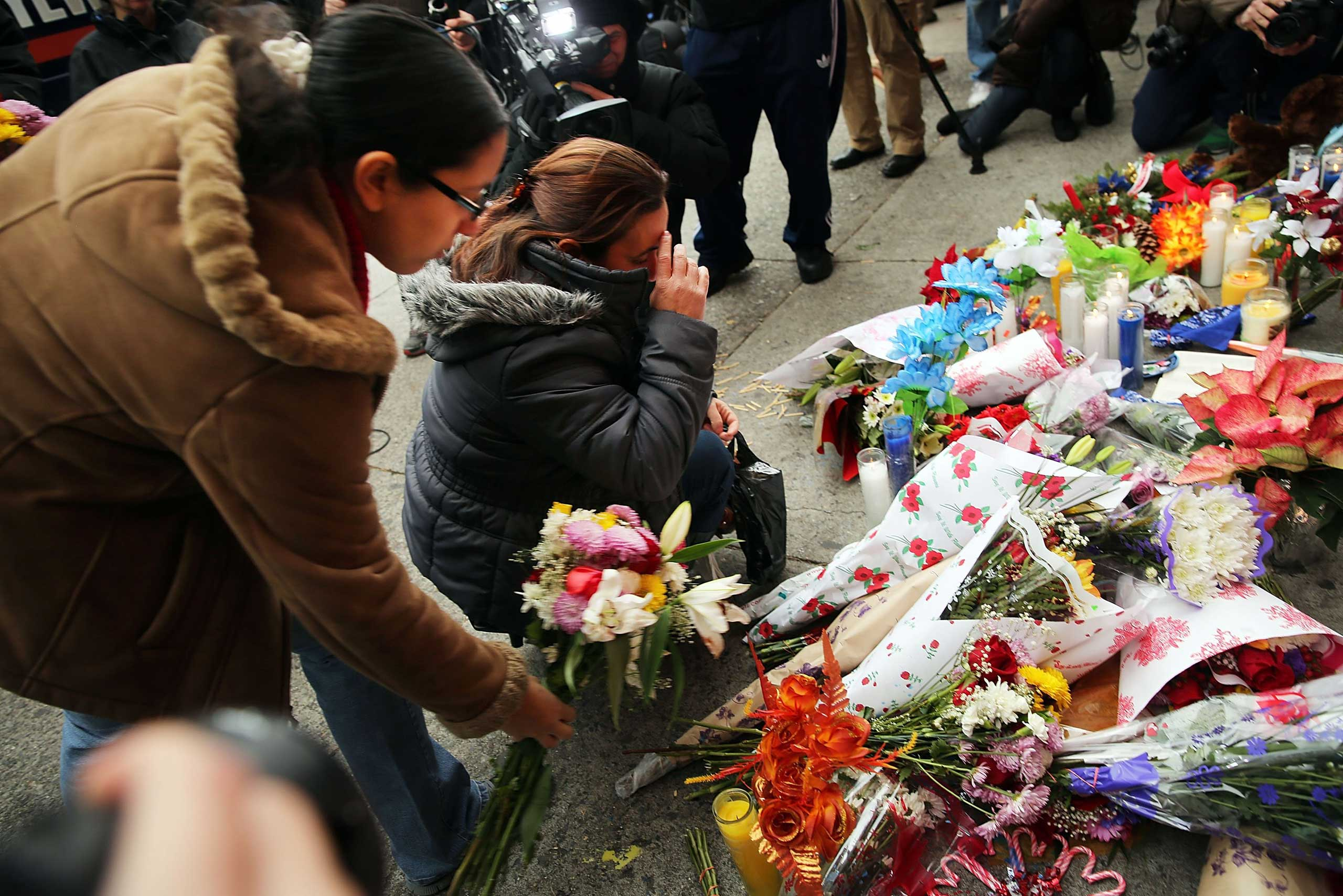 Women place flowers at a memorial to the two New York Police Department (NYPD) officers that were shot and killed nearby Dec. 21, 2014 in the Bedford Stuyvesant neighborhood of the Brooklyn borough of New York City.