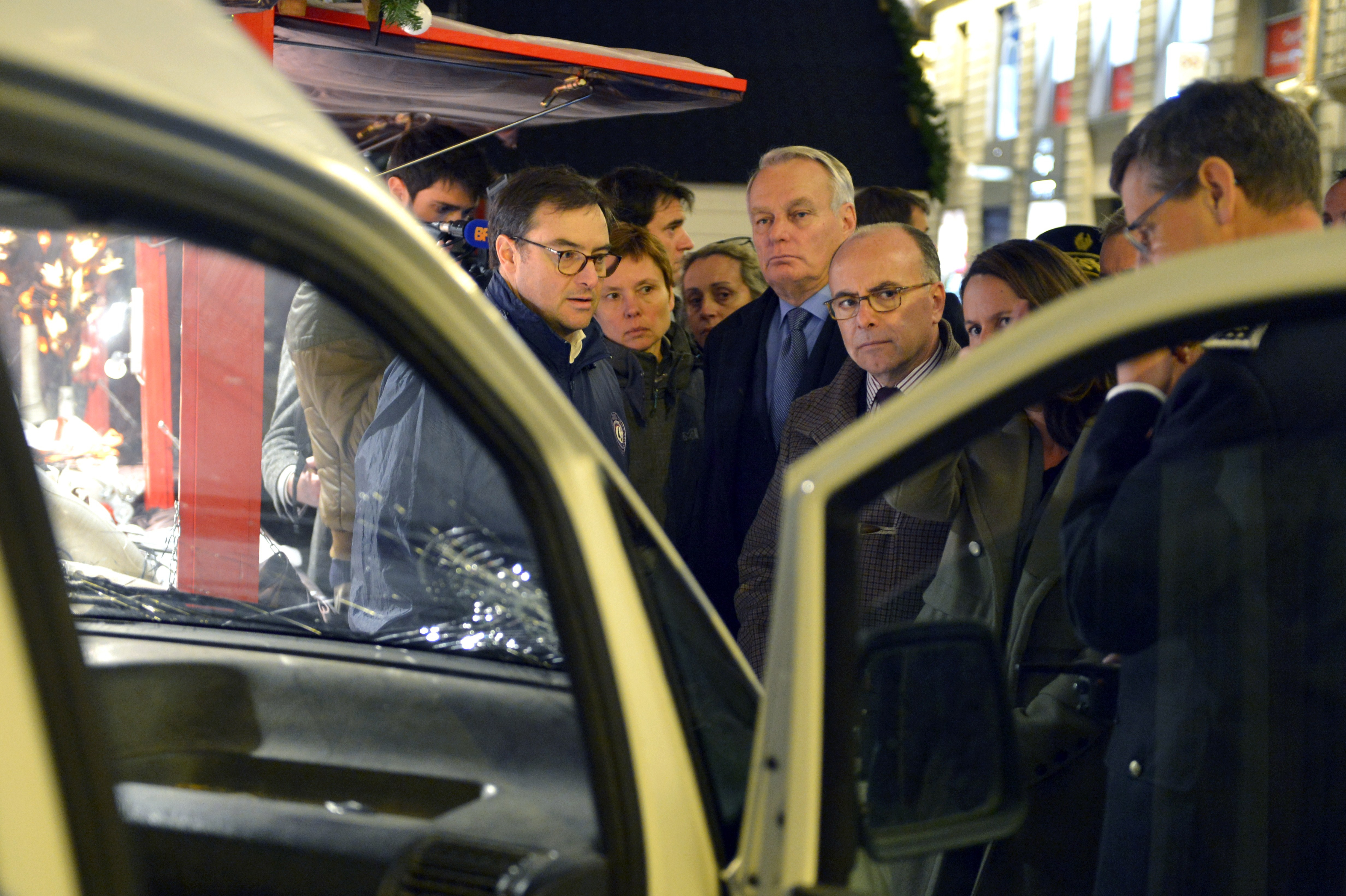 French Interior Minister (C) and French socialist member of Parliament and former Prime Minister Jean-Marc Ayrault (C-R) inspect the van a driver used to plough into a Christmas market in the western French city of Nantes on December 22, 2014.
