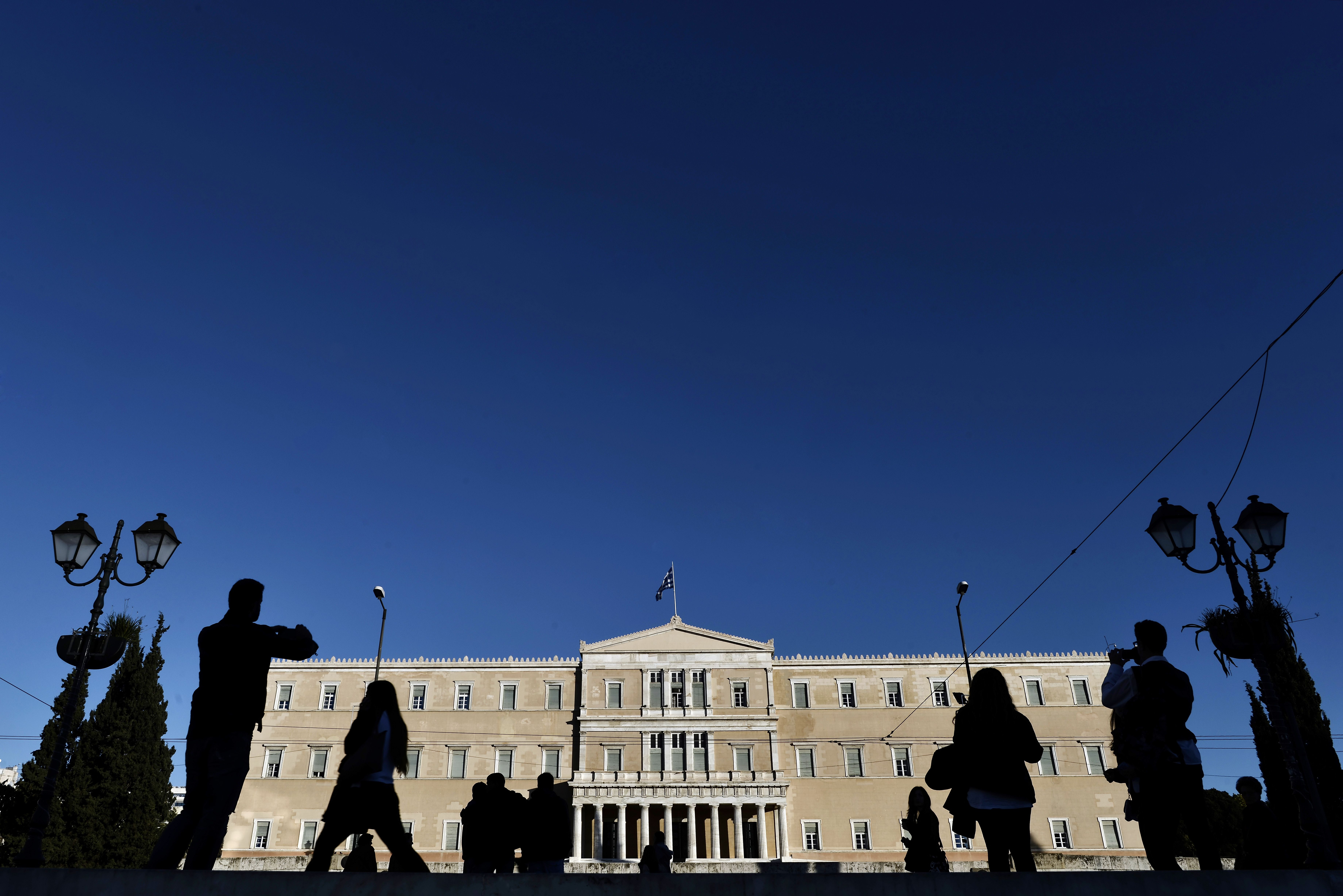 People walk past the Greek Parliament in Athens on Dec. 17, 2014. Greece is a step away from early elections that could repudiate its international bailout and rekindle a euro-zone crisis after lawmakers failed to elect a President