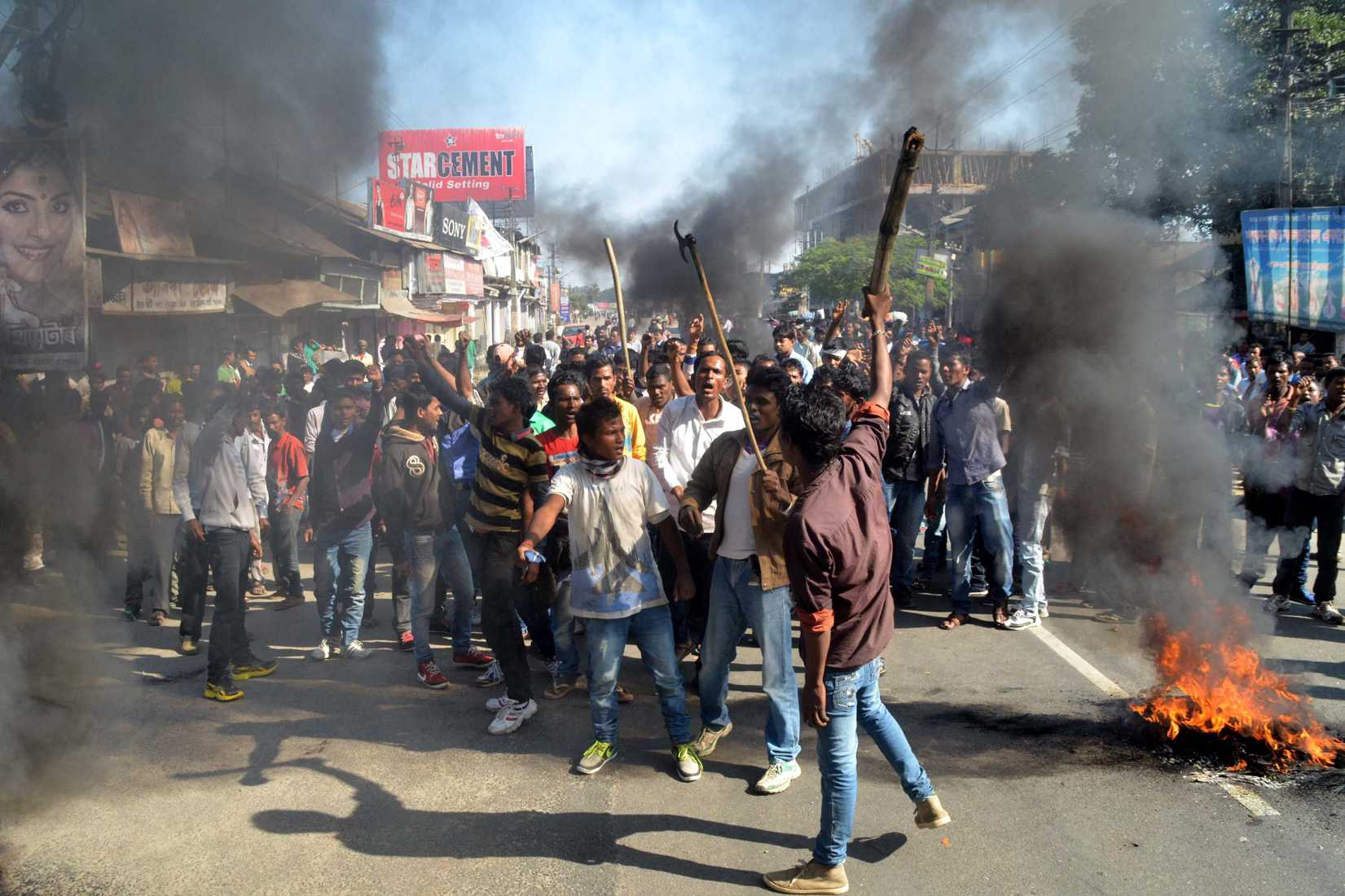 Activists of the Assam Tea Tribes Student Association (ATTSA) shout slogans as they block the road with burning tyres during a protest against attacks on villagers by militants in four different locations, at Biswanath Chariali in the Sonitpur district of northeastern Assam state on December 24, 2014