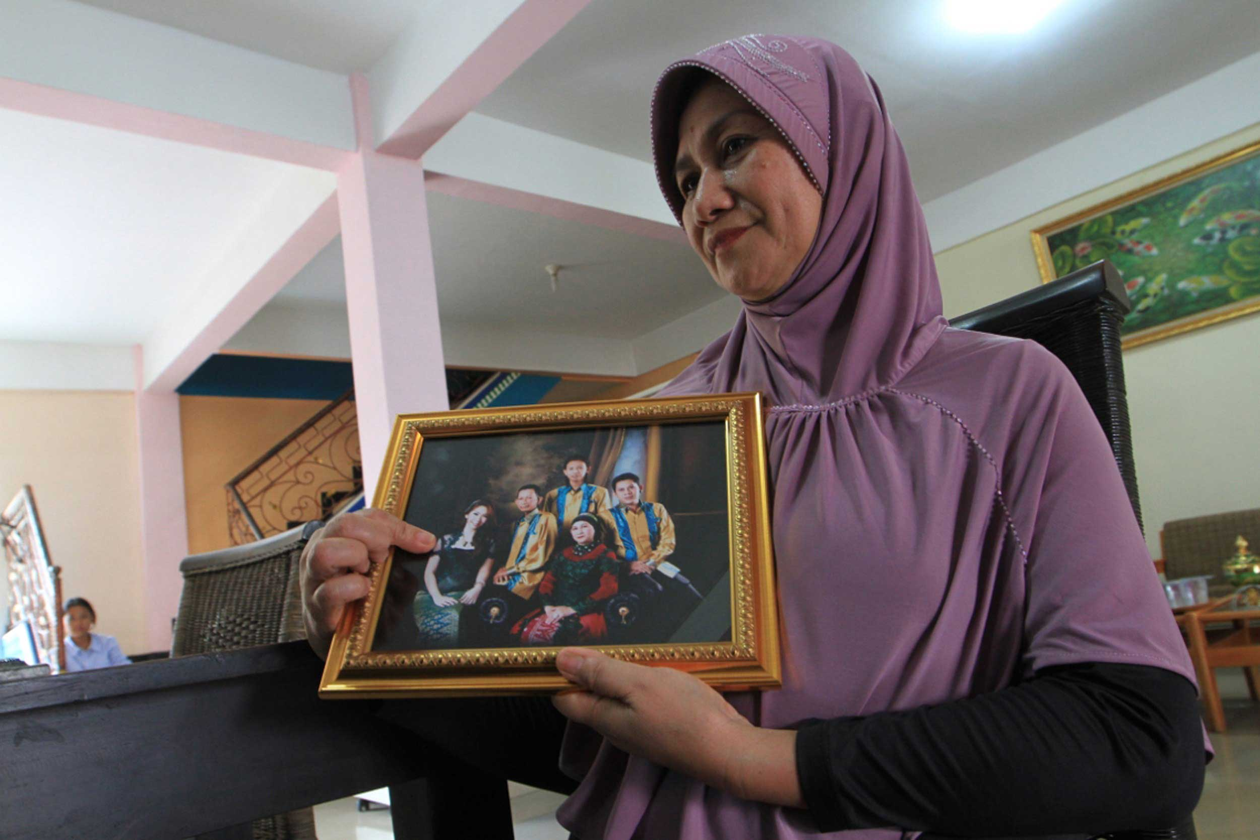 Rohana, the mother of Khairunisa, a flight attendant who was travelling on missing Air Asia Flight QZ 8501, points towards her daughter, left, within a framed family photograph in Palembang, South Sumatra, on Dec. 28, 2014.