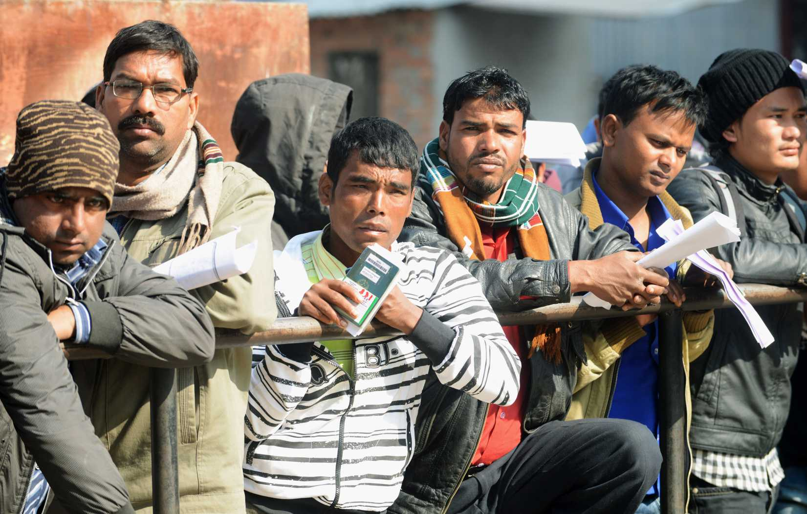 Nepalese migrant workers queue to receive official documents in order to leave Nepal from the Labour department in Kathmandu on January 27, 2014.