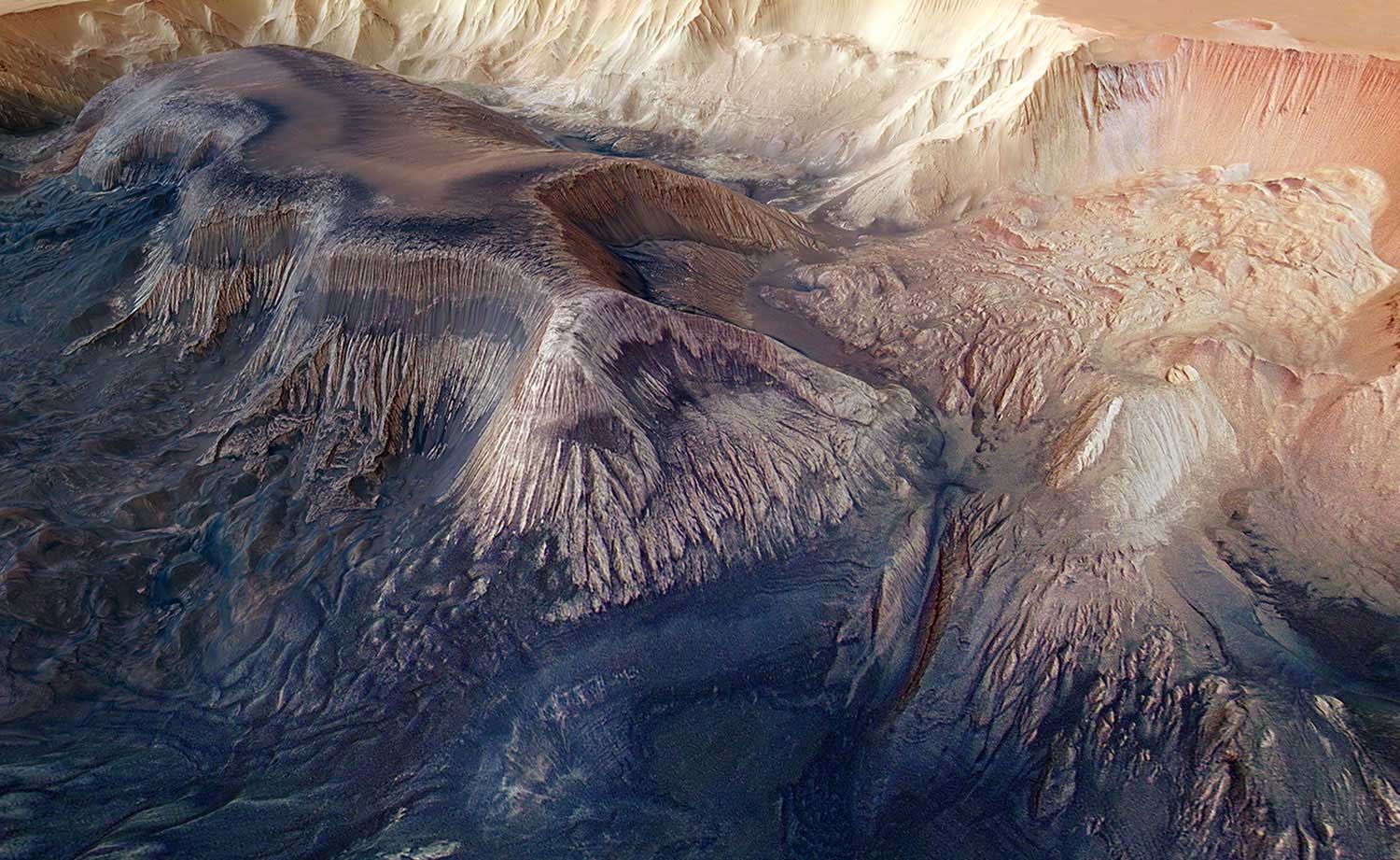 A flat-topped mesa is located in the center of Hebes Chasma on Mars and rises to a similar height as the surrounding plains. Exposed within the walls of the mesa are layers of sediments deposited by wind and water. Numerous grooves are etched into the mountain, suggesting the material is weak and easily eroded.