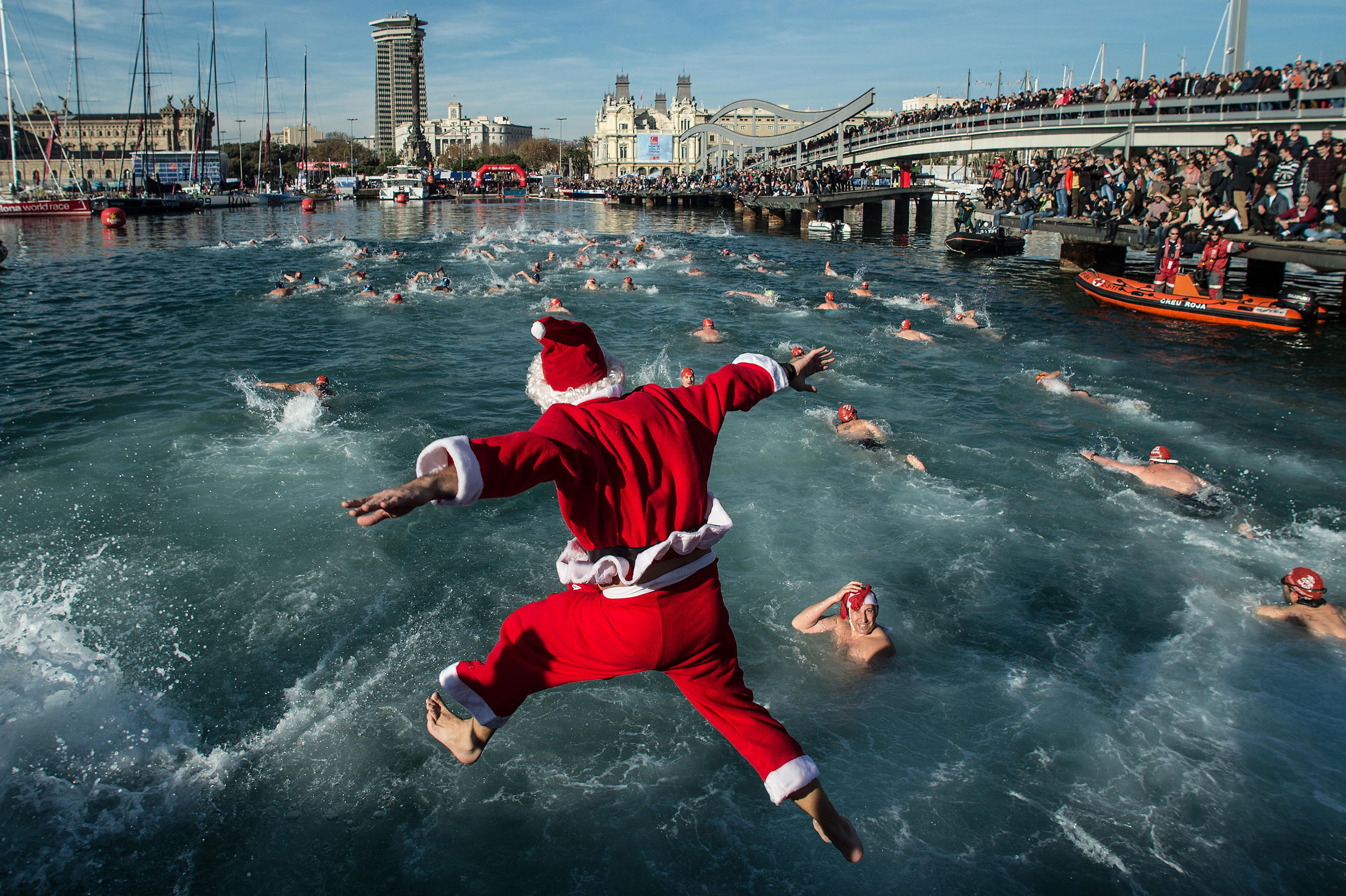 A competitor in Christmas fancy dress jumps into the sea during the 105th Barcelona Traditional Christmas Swimming Cup at the Old Harbour of Barcelona on Dec. 25, 2014 in Barcelona. The Copa Nadal is organised by the Barcelona Swimming Club and involves competitors swimming across some 200 metres of water in the harbour.