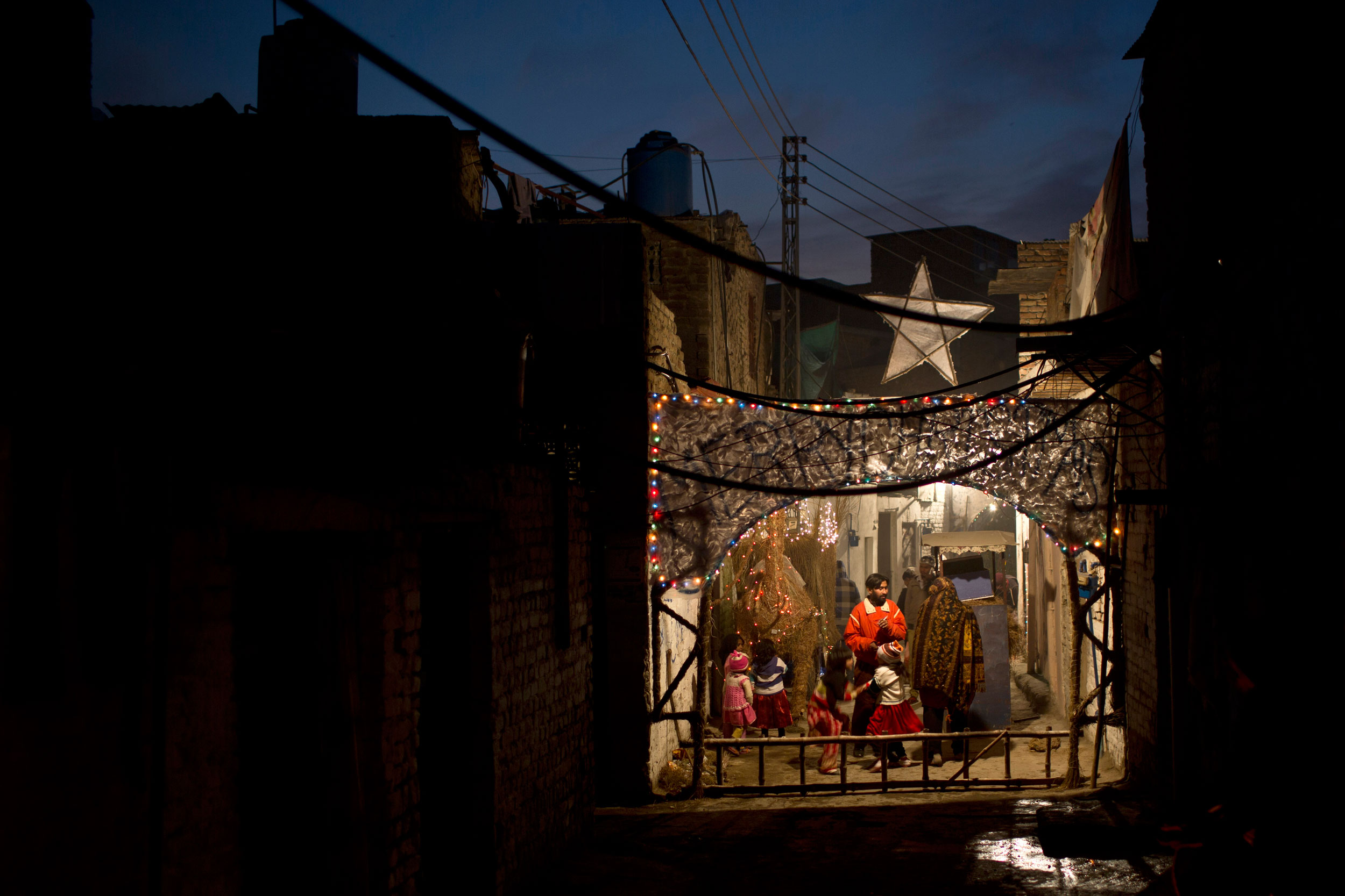 Pakistani Christians gather in an alley of a Christian neighborhood decorated with festive lights for Christmas in Islamabad, Pakistan on Dec. 24, 2014.