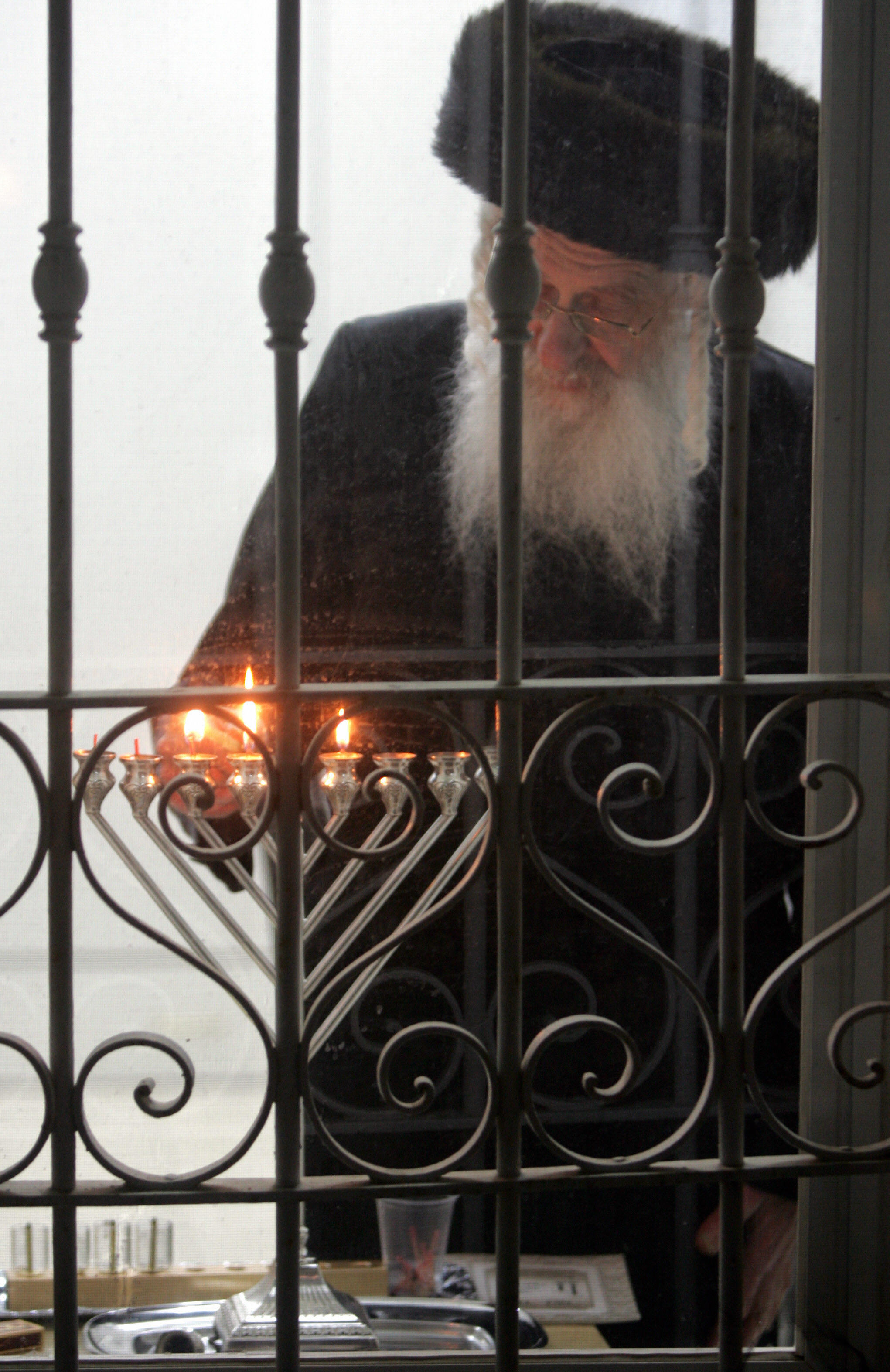 An Ultra-Orthodox Jewish man lights the candles of the fifth night of the Jewish holiday of Hanukah, in the ultra-Orthodox neighborhood of Mea Shearim in Jerusalem.