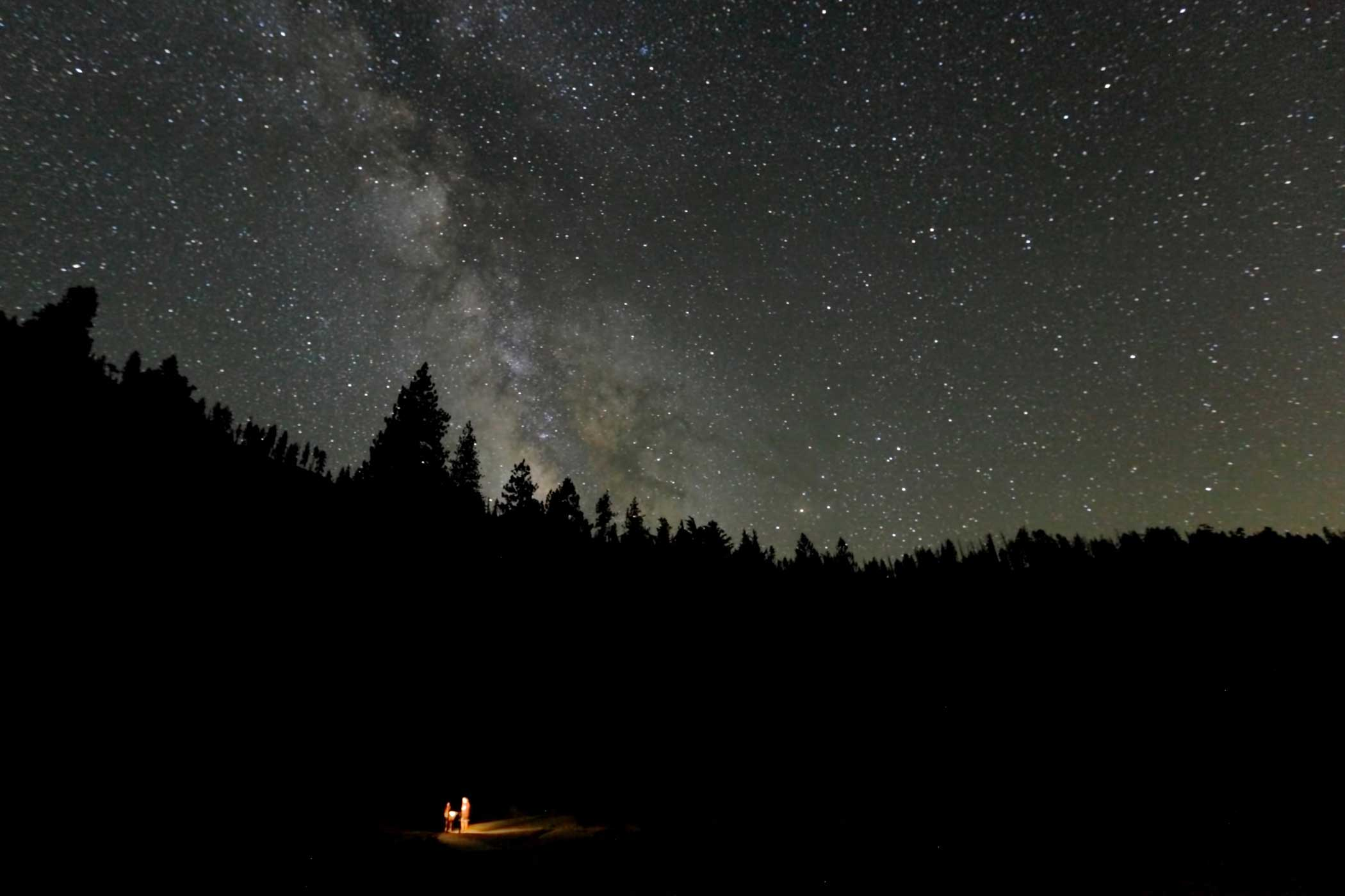 The photographer came across two hikers lost in the wilderness of Yosemite late one evening in July 2011. He captured this image of the tiny figures in a small bubble of torchlight set within a vast, pitch black forest beneath the immense dome of the sky. It highlights the wonder, beauty and awe of astronomy.