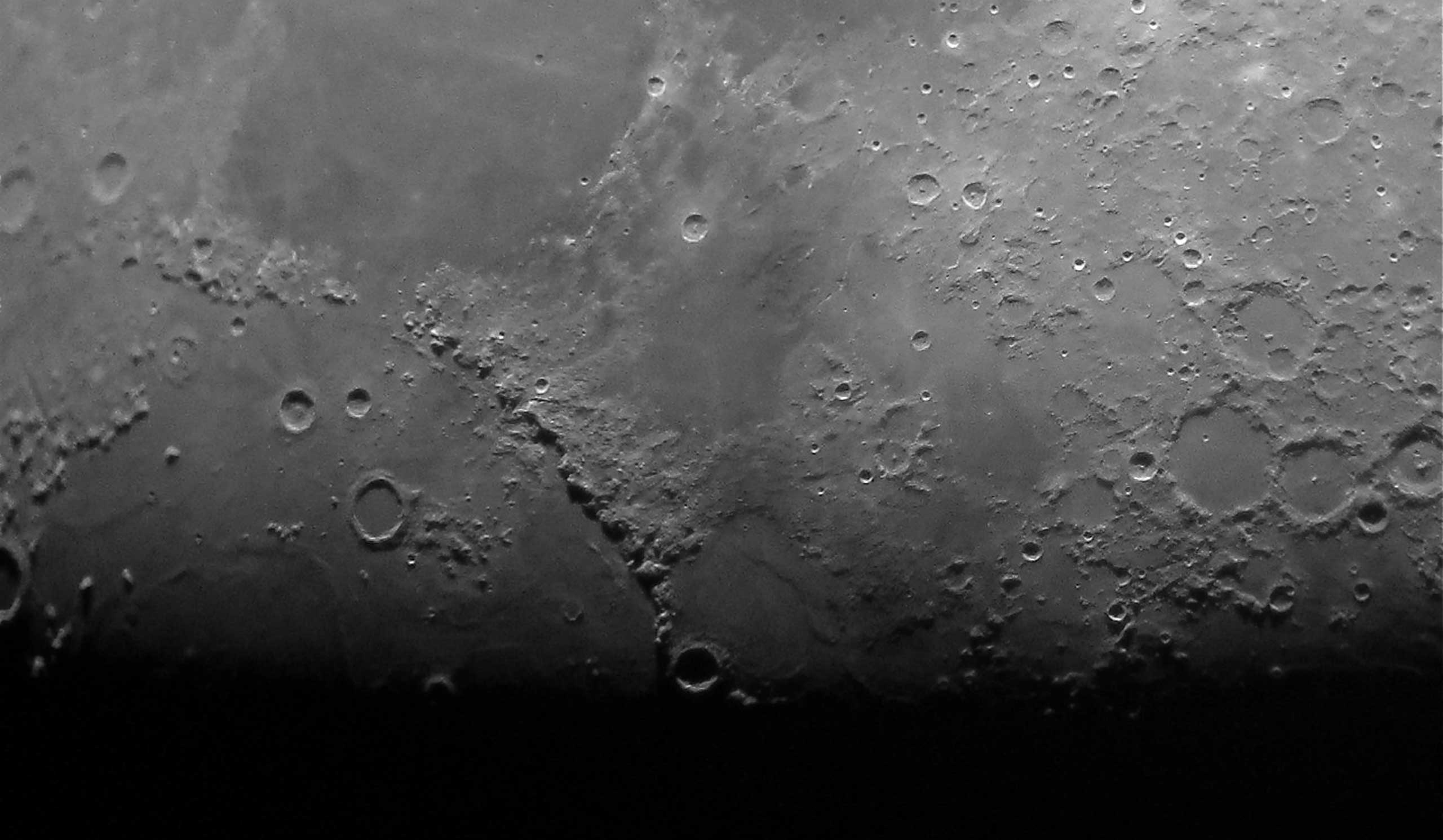 A beautifully sharp and artfully framed detail of the Moon. The terminator which separates the daytime and night-time parts of the Moon is aligned with the bottom edge of the photograph.  The Sun's light shines at a low angle onto the surface of the Moon just above this line, showing the contrast between smooth maria and rugged crater rims to the best advantage.
