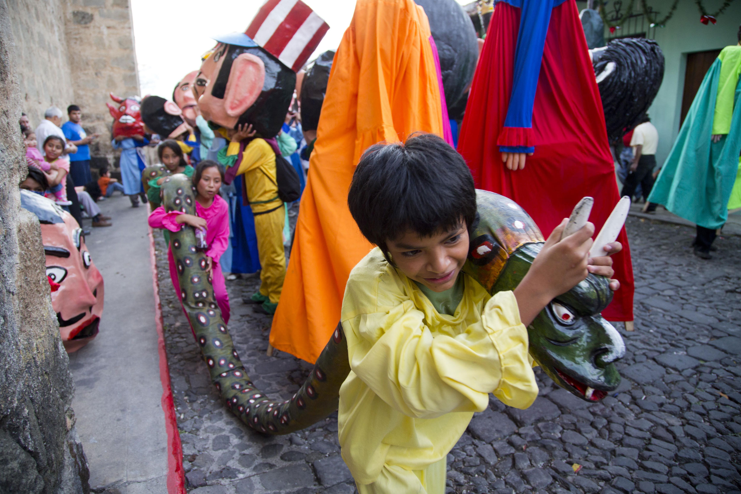 Children carry a snake made out of rags and paper mache as they take part in the traditional dance of  Los Gigantes,  or  The Giants,  during Christmas celebrations on Christmas Eve in Antigua Guatemala on Dec. 24, 2014.