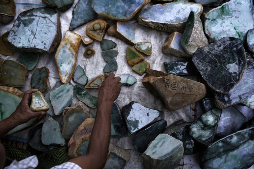 A Burmese dealer arranges chunks of jade at a market stall in Mandalay.
