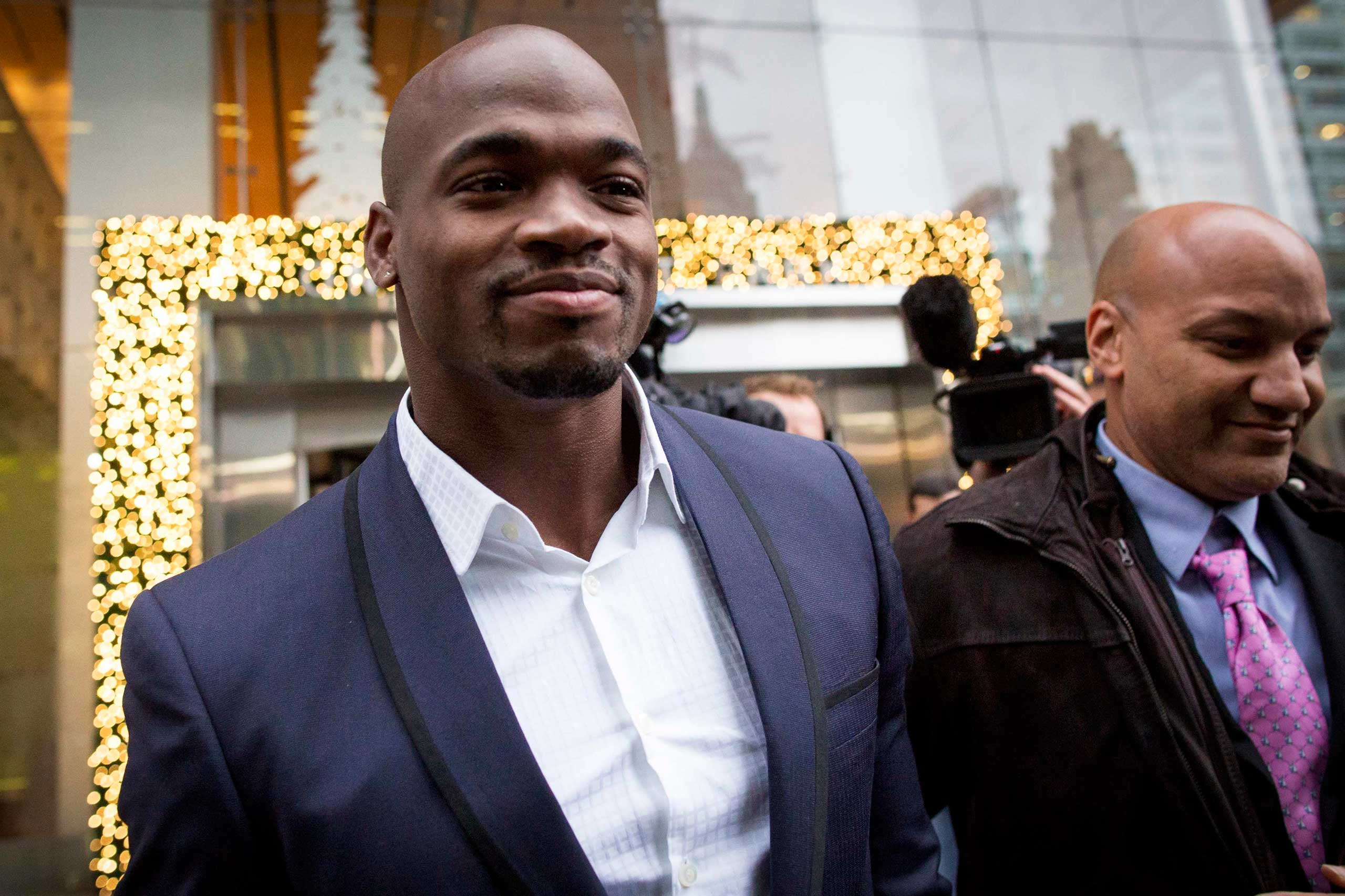 Suspended Minnesota Vikings running back Adrian Peterson (L) exits following his hearing against the NFL over his punishment for child abuse, in  New York City on Dec. 2, 2014.