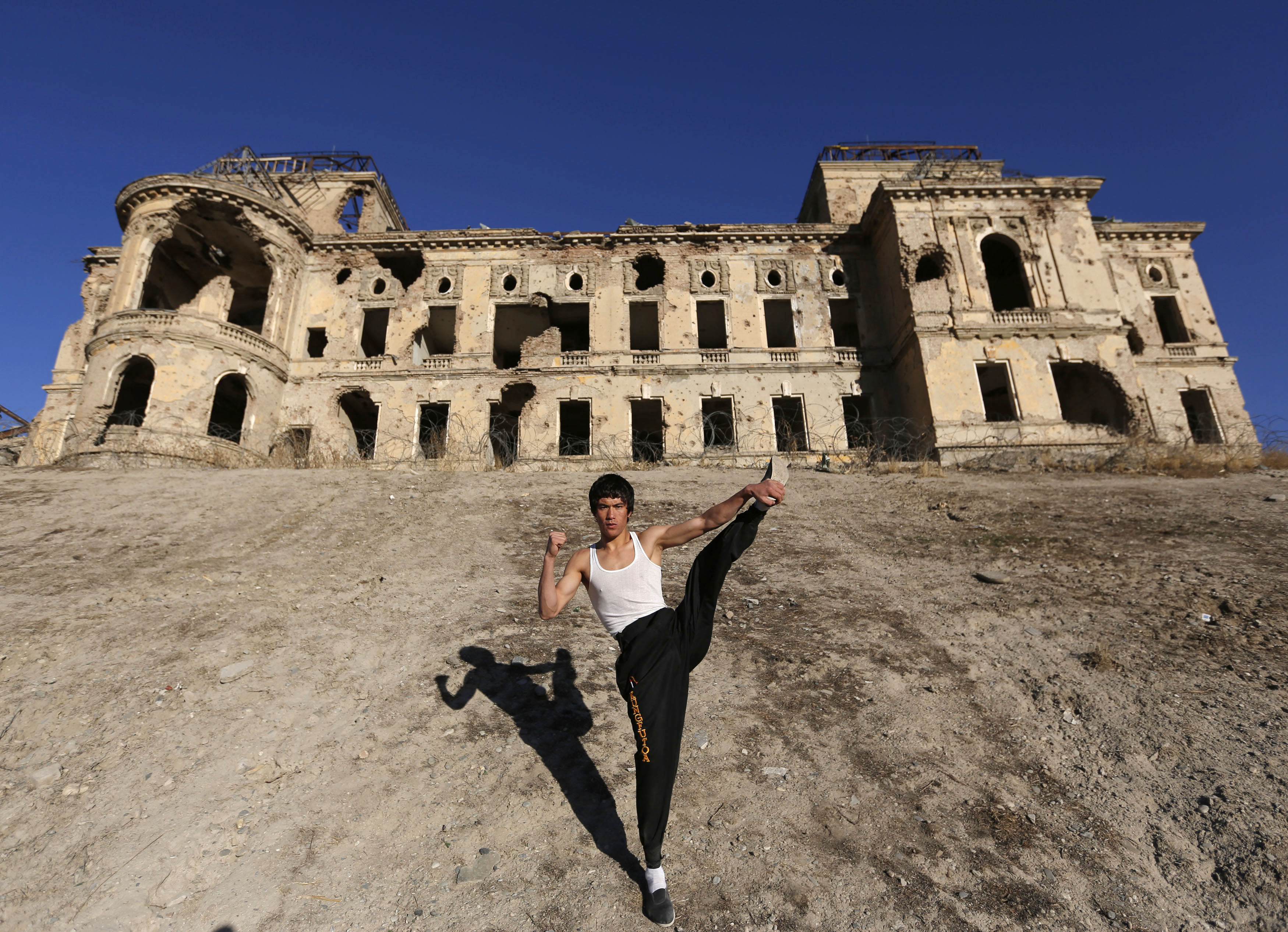 Abbas Alizada who calls himself the Afghan Bruce Lee poses for the media in front of the destroyed Darul Aman Palace in Kabulon Dec. 9, 2014.