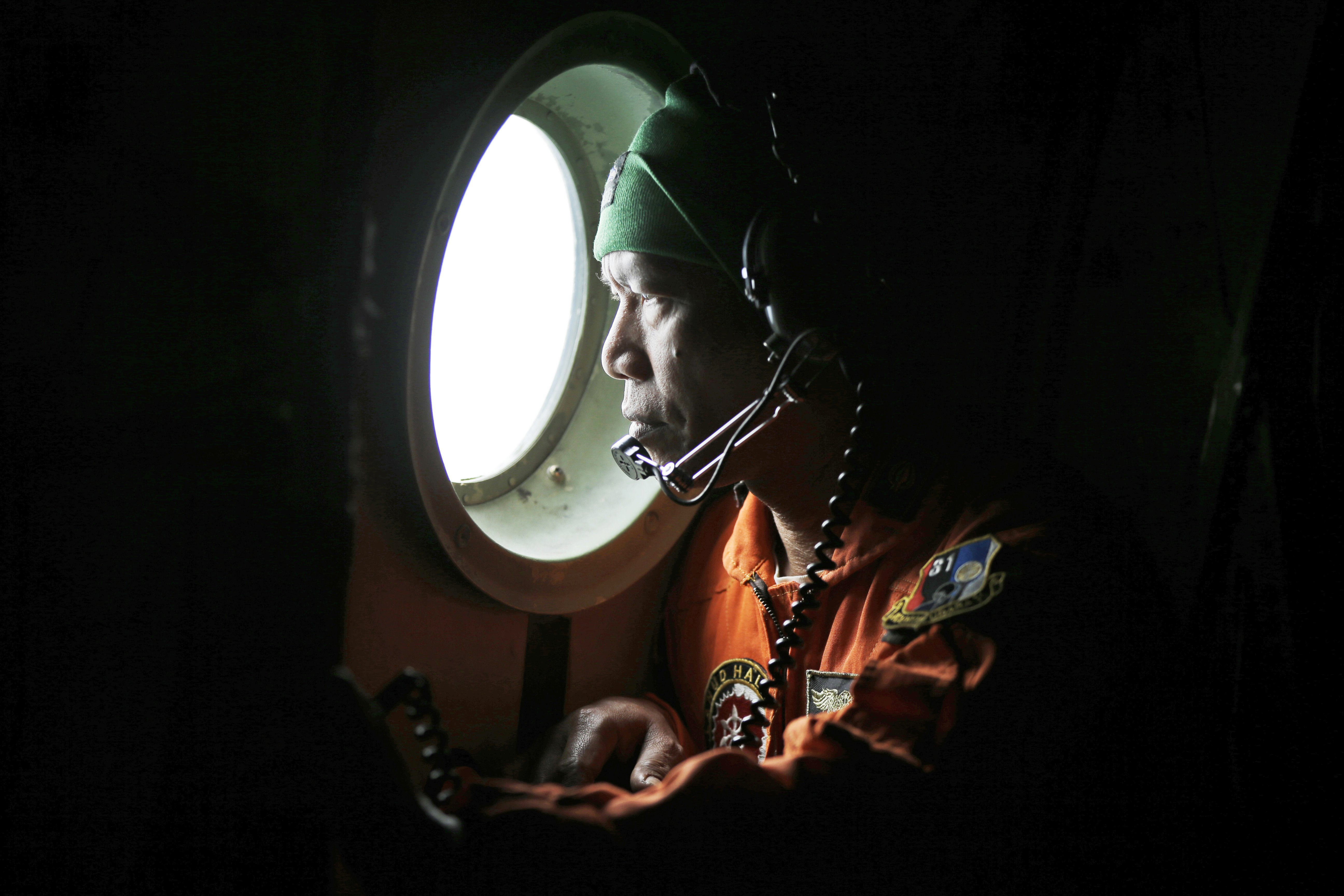 A crew member of the Indonesian air force's C-130 airplane looks out of the window during a search operation for the missing AirAsia Flight QZ 8501 jetliner over the waters of Karimata Strait in Indonesia on Dec. 29, 2014
