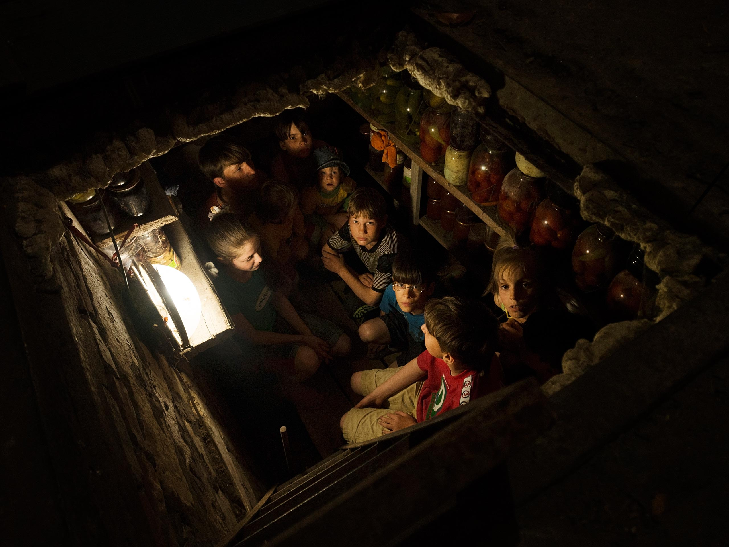 A family gives shelter to 10 orphans seeking refuge from overnight bombing in their basement in Slovyansk, Ukraine, on May 14, 2014.