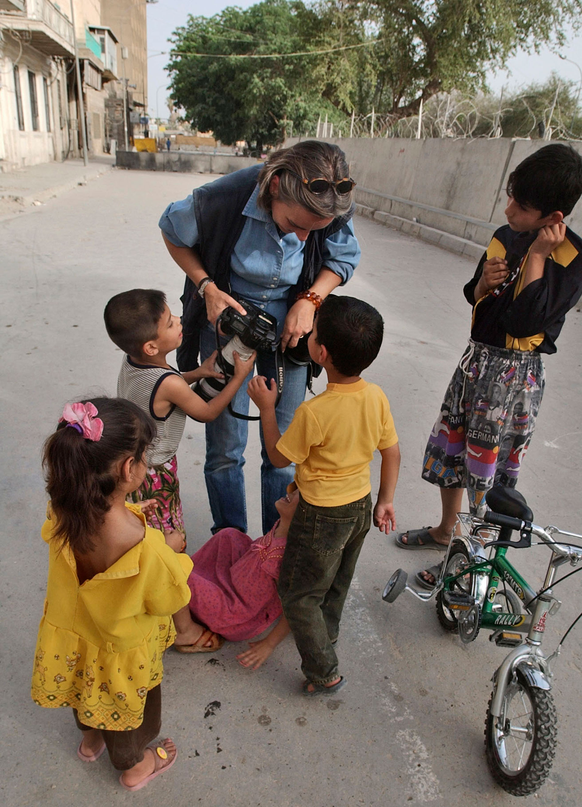 Anja Niedringhaus shows Iraqi children their pictures in Baghdad in 2004.