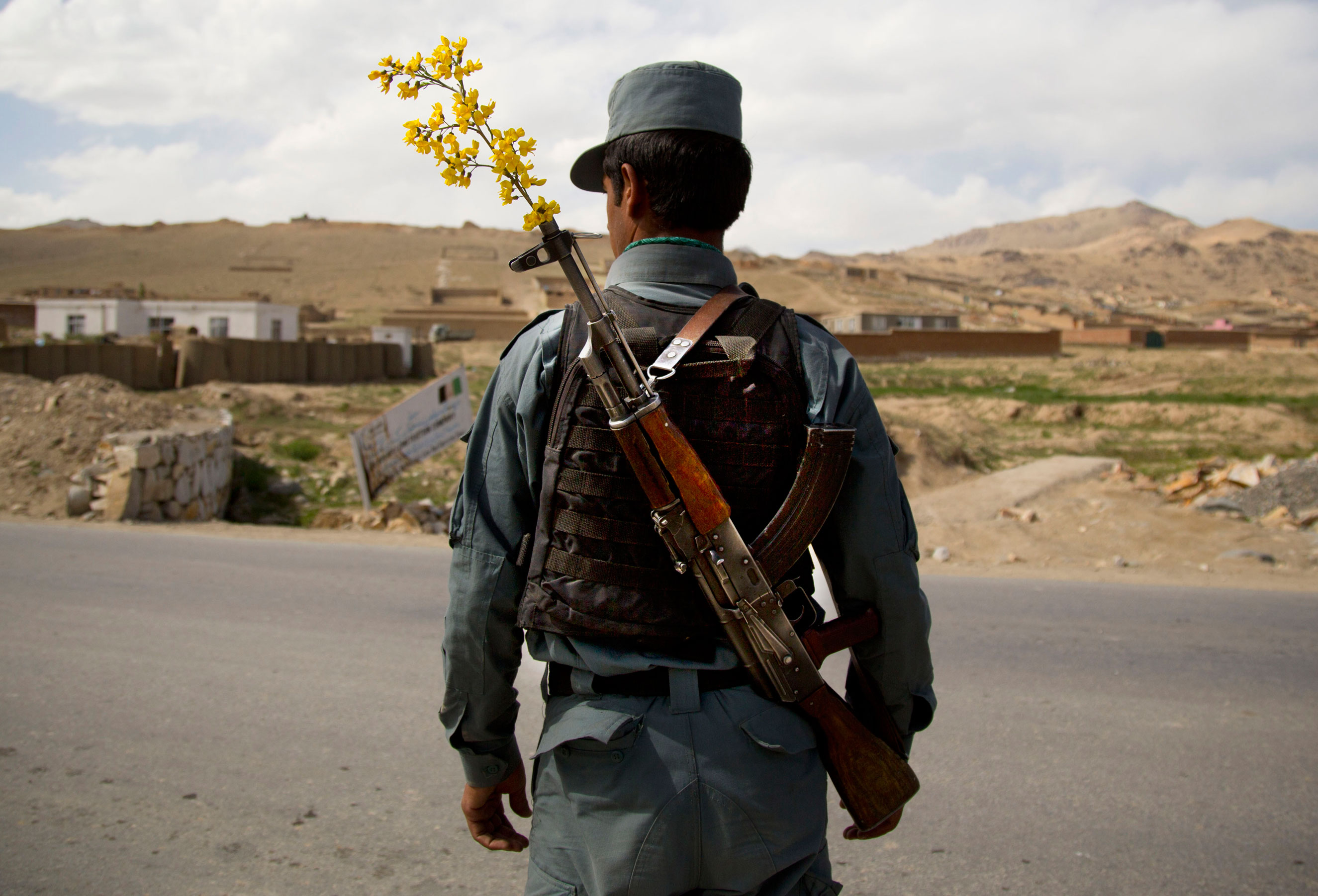 An Afghan National Police officer mans a checkpoint on the outskirts of Maidan Shahr, Wardak province, on May 15, 2013.