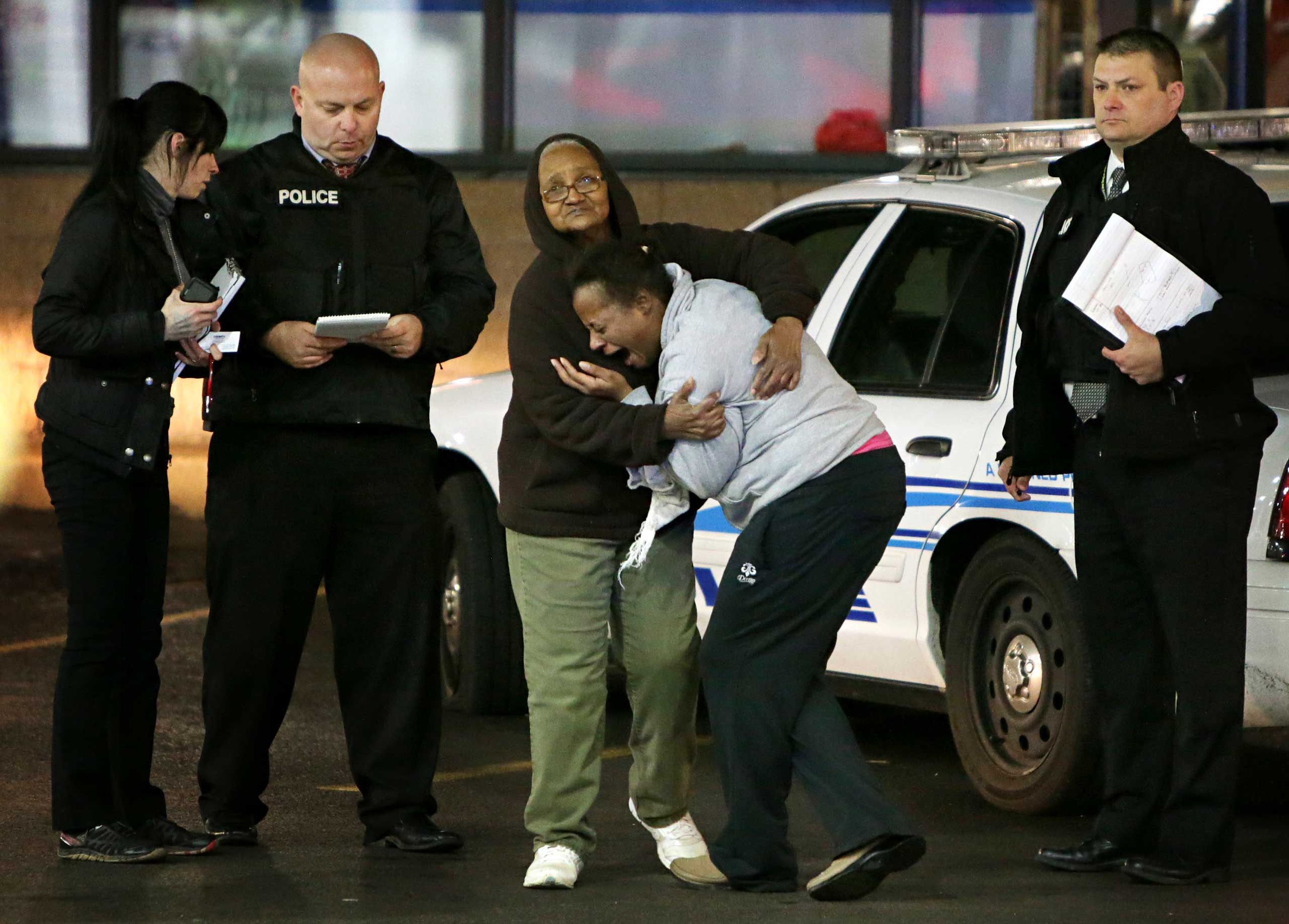 Toni Martin cries out on Dec. 24, 2014 as she talks to police at the scene where she says her son was fatally shot at a gas station in Berkeley, Mo.