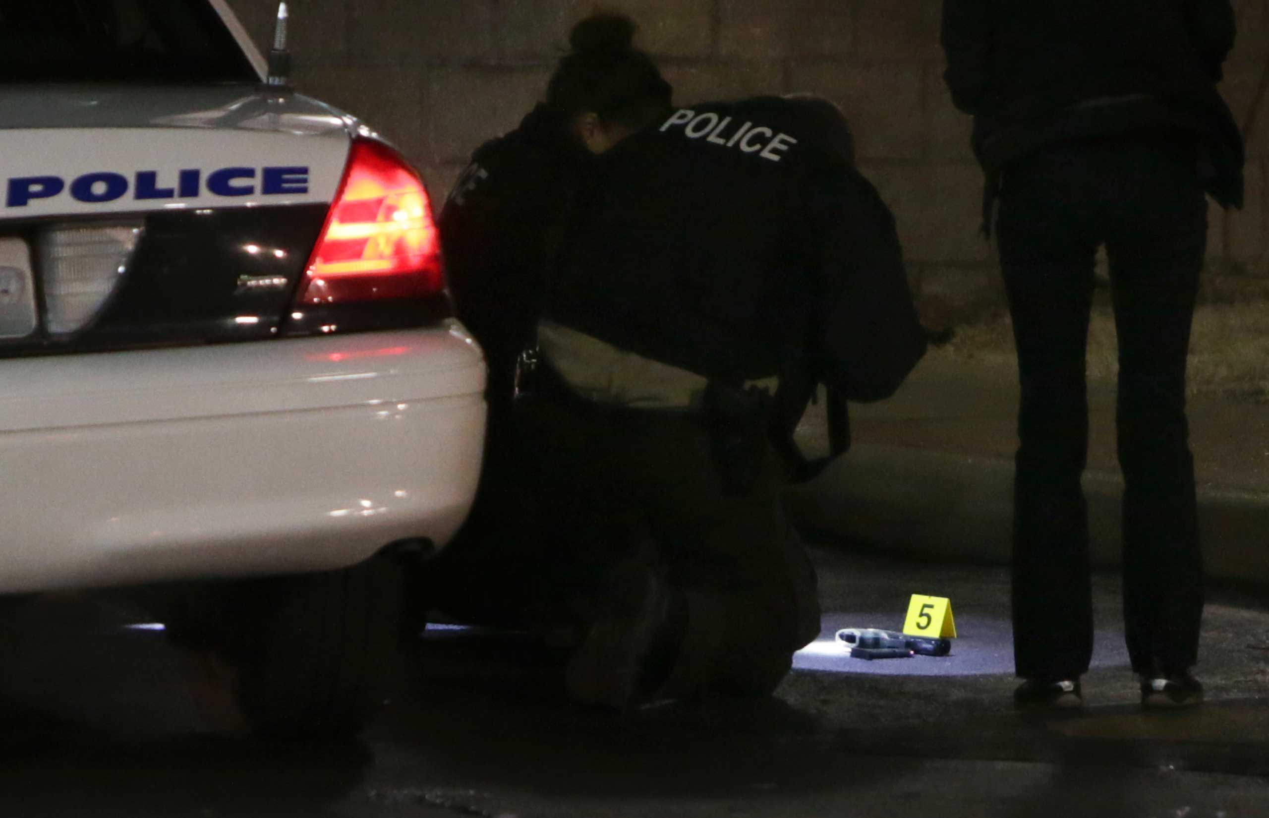 Police photograph a gun on the ground on Dec. 24, 2014 following a shooting at a gas station in Berkeley, Mo.