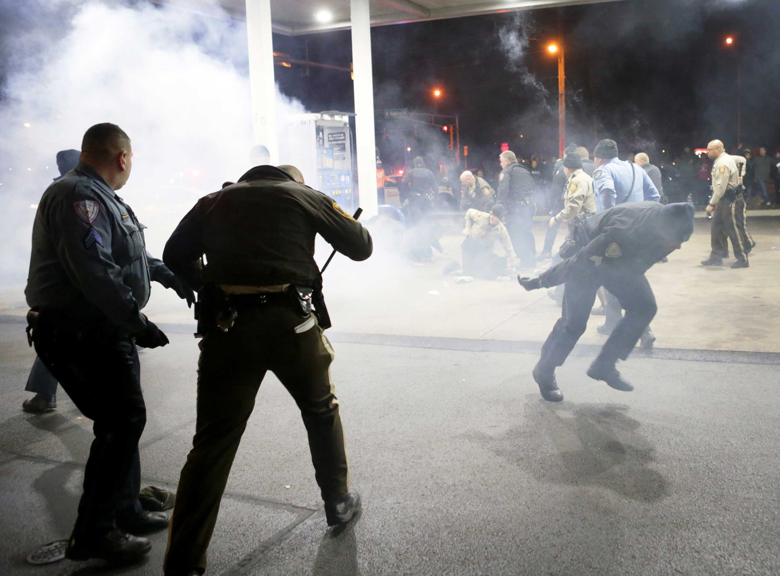 Police try to control a crowd on Dec. 24, 2014, on the lot of a gas station following a shooting in Berkeley, Mo.