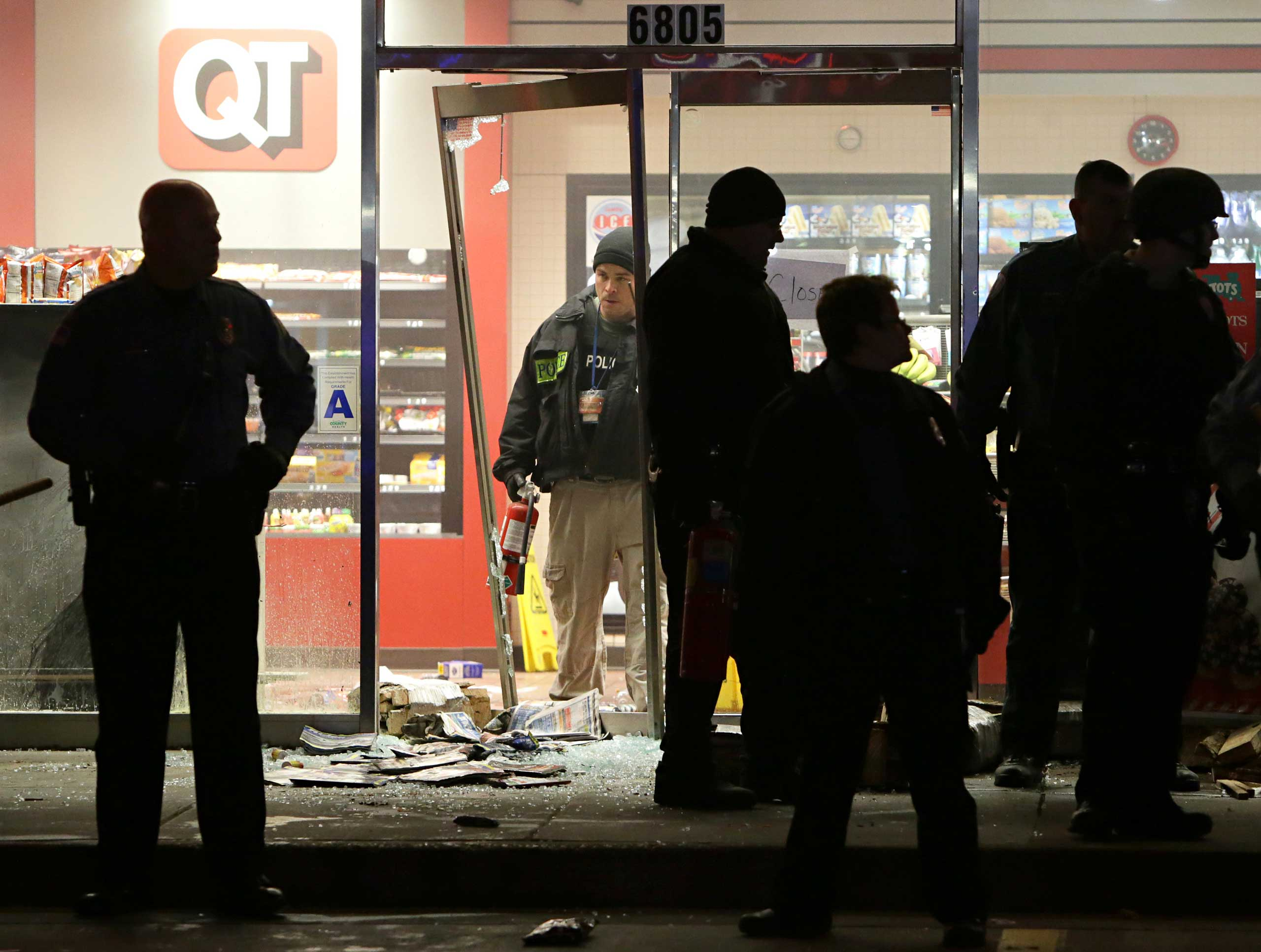 A police officer with a fire extinguisher stands in the broken out entry to a QuikTrip on Dec. 24, 2014 following a shooting nearby in Berkeley, Mo.